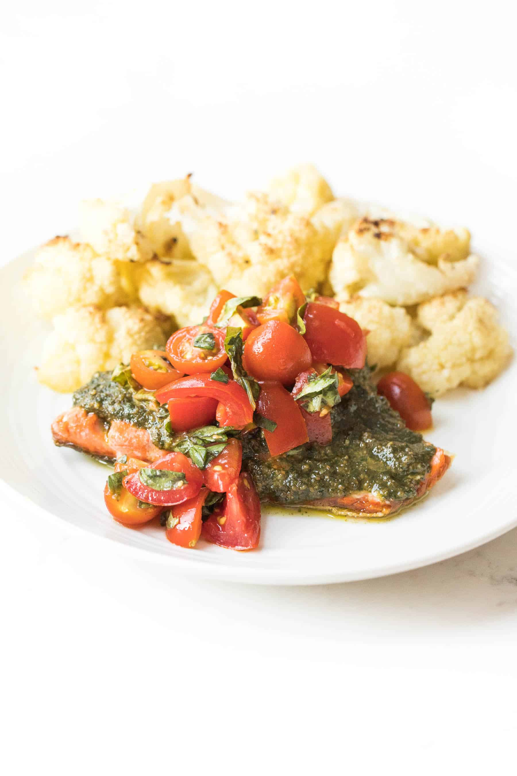 salmon topped with pesto and tomatoes on a white plate and white background