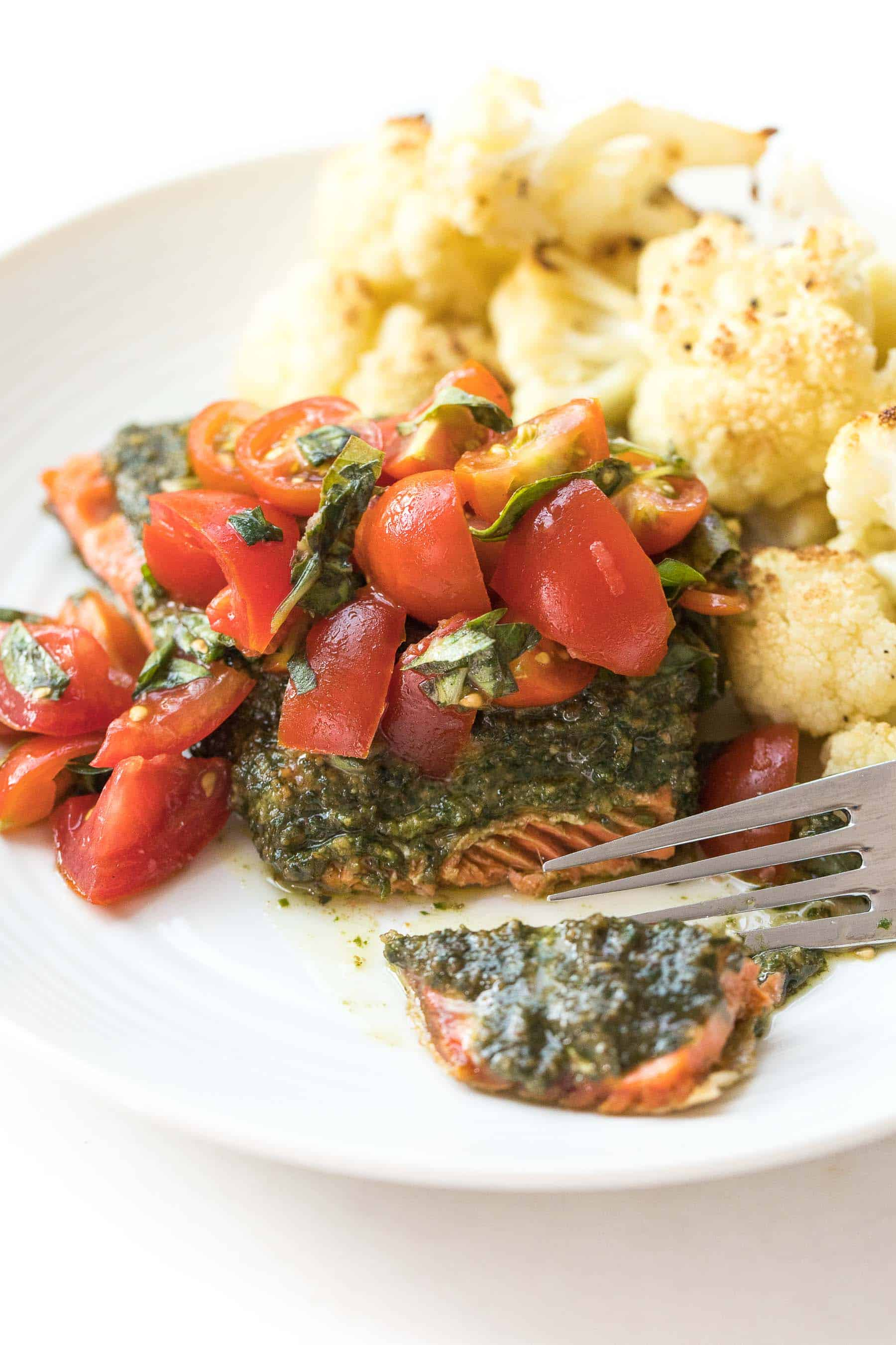fork cutting salmon topped with pesto and tomatoes on a white plate and white background