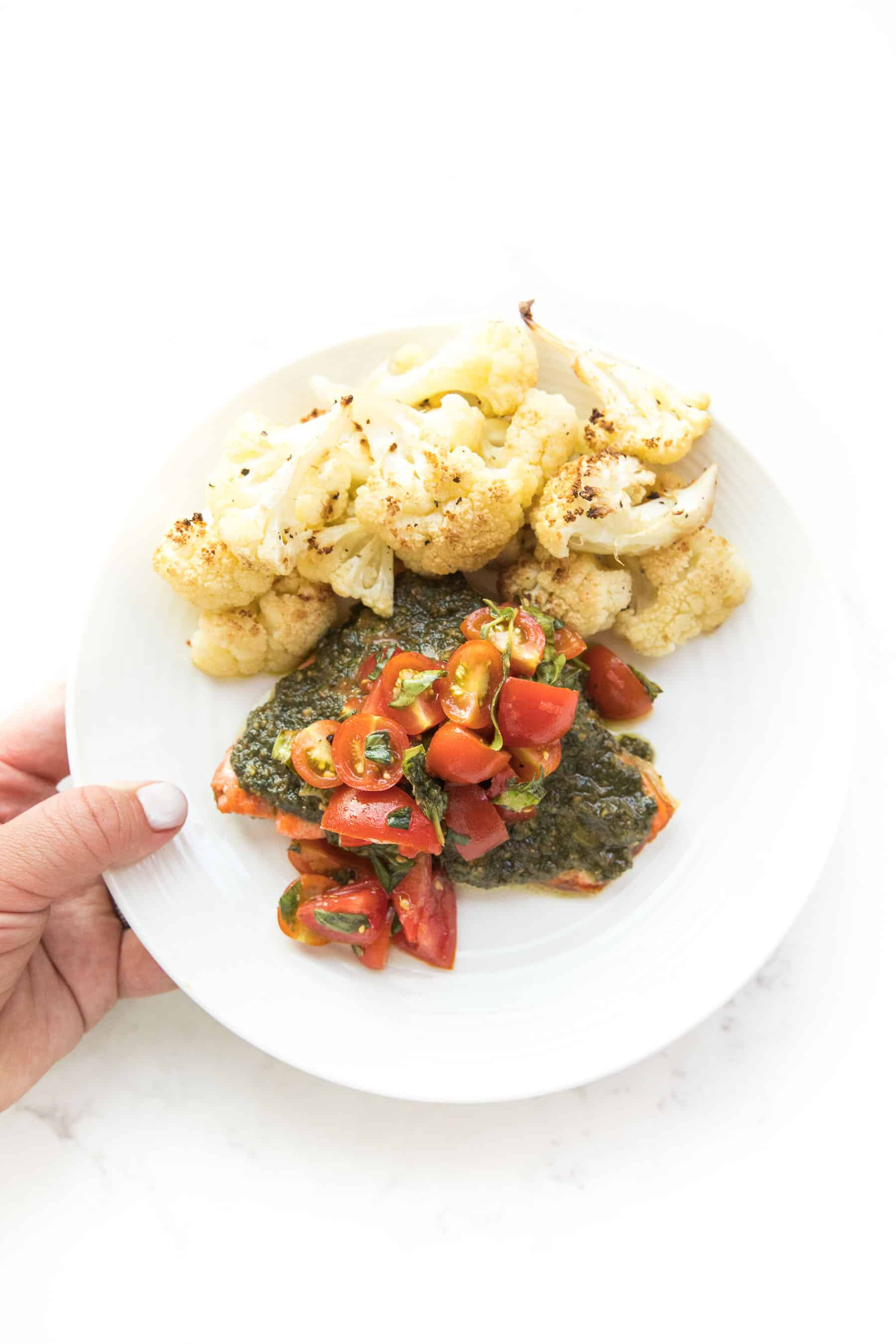 hand holding salmon topped with pesto and tomatoes on a white plate and white background