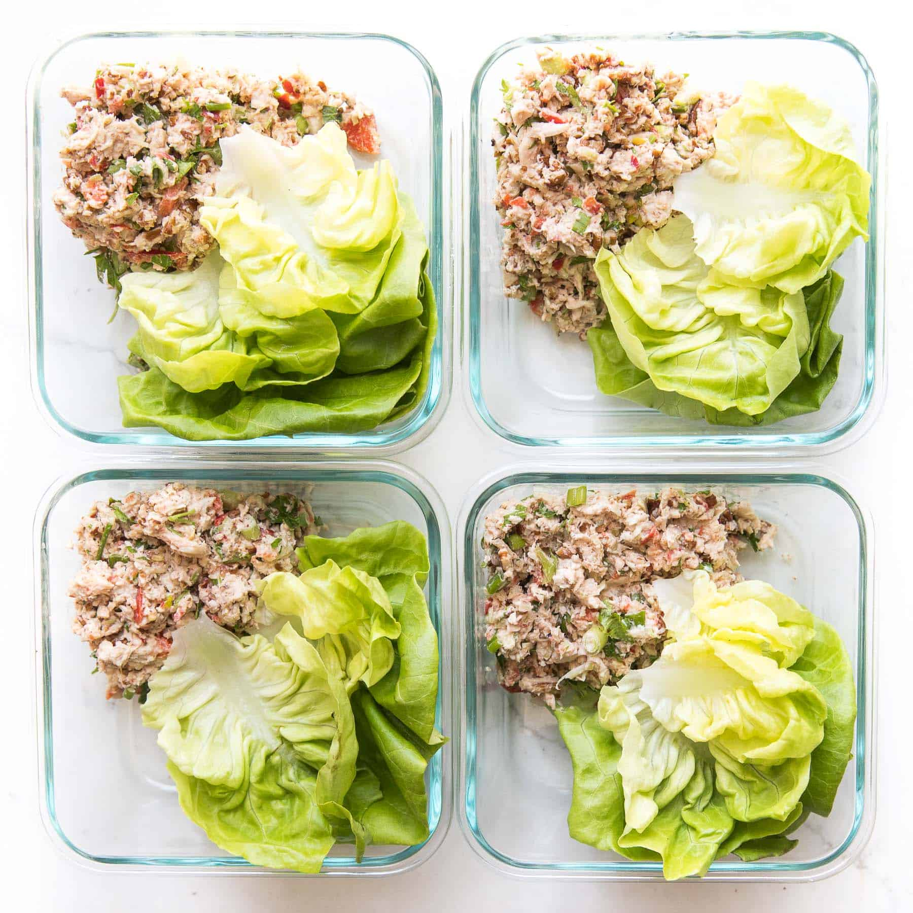 chicken salad and butter lettuce in meal prep containers on a white background
