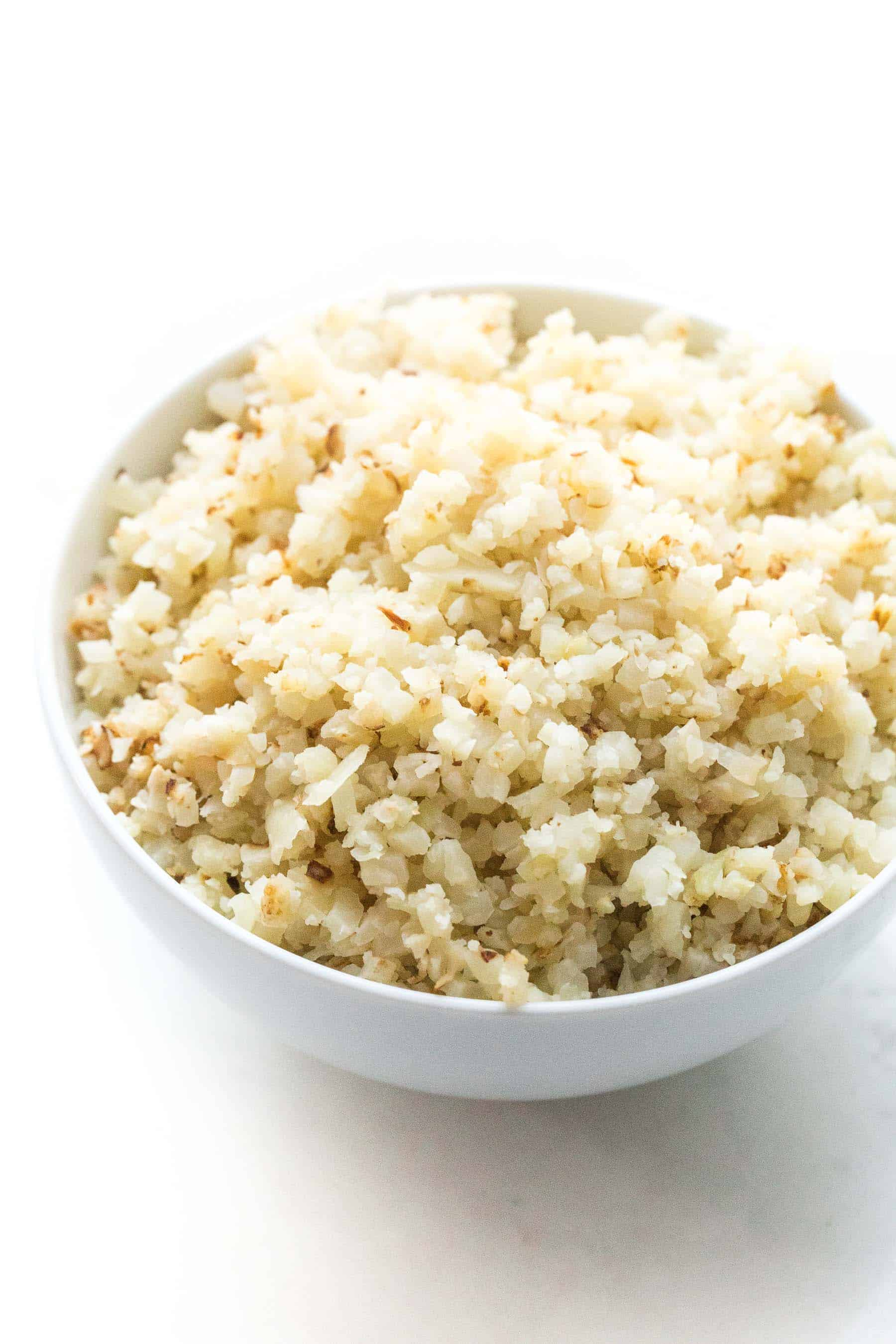 cauliflower rice in a white bowl on a white background