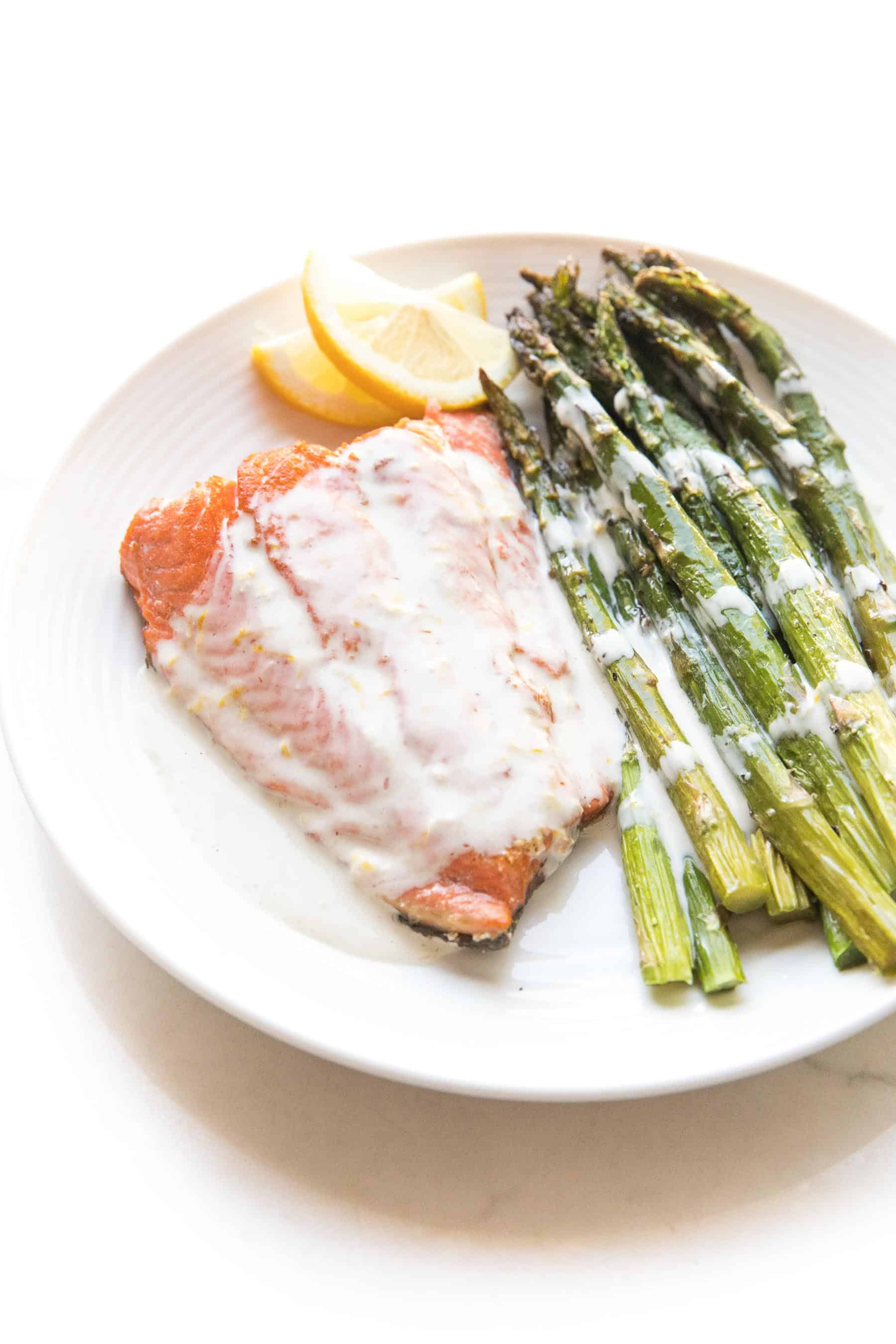 Salmon + asparagus with a white creamy coconut tahini sauce on a white plate and background