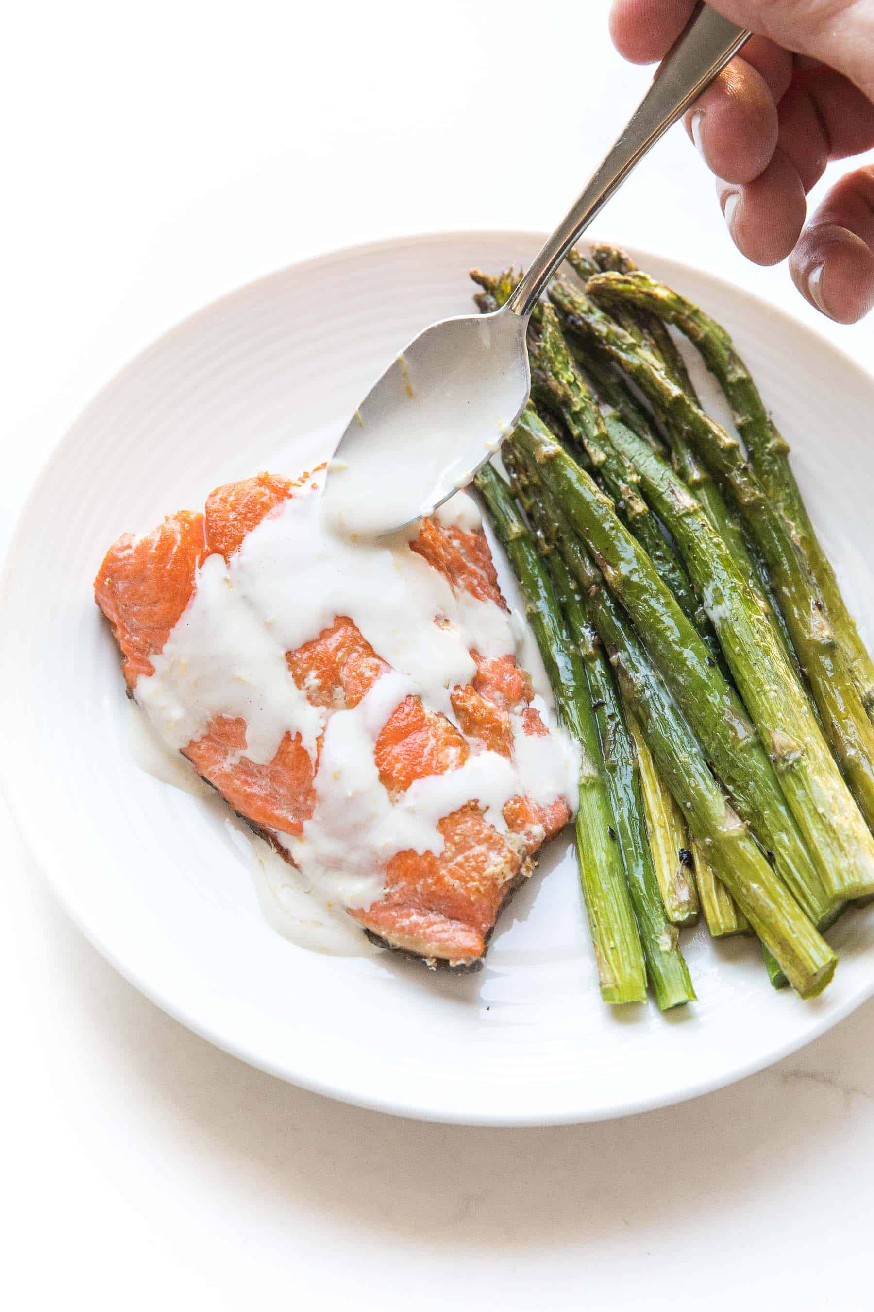 spoon drizzling Salmon + asparagus with a white creamy coconut tahini sauce on a white plate and background