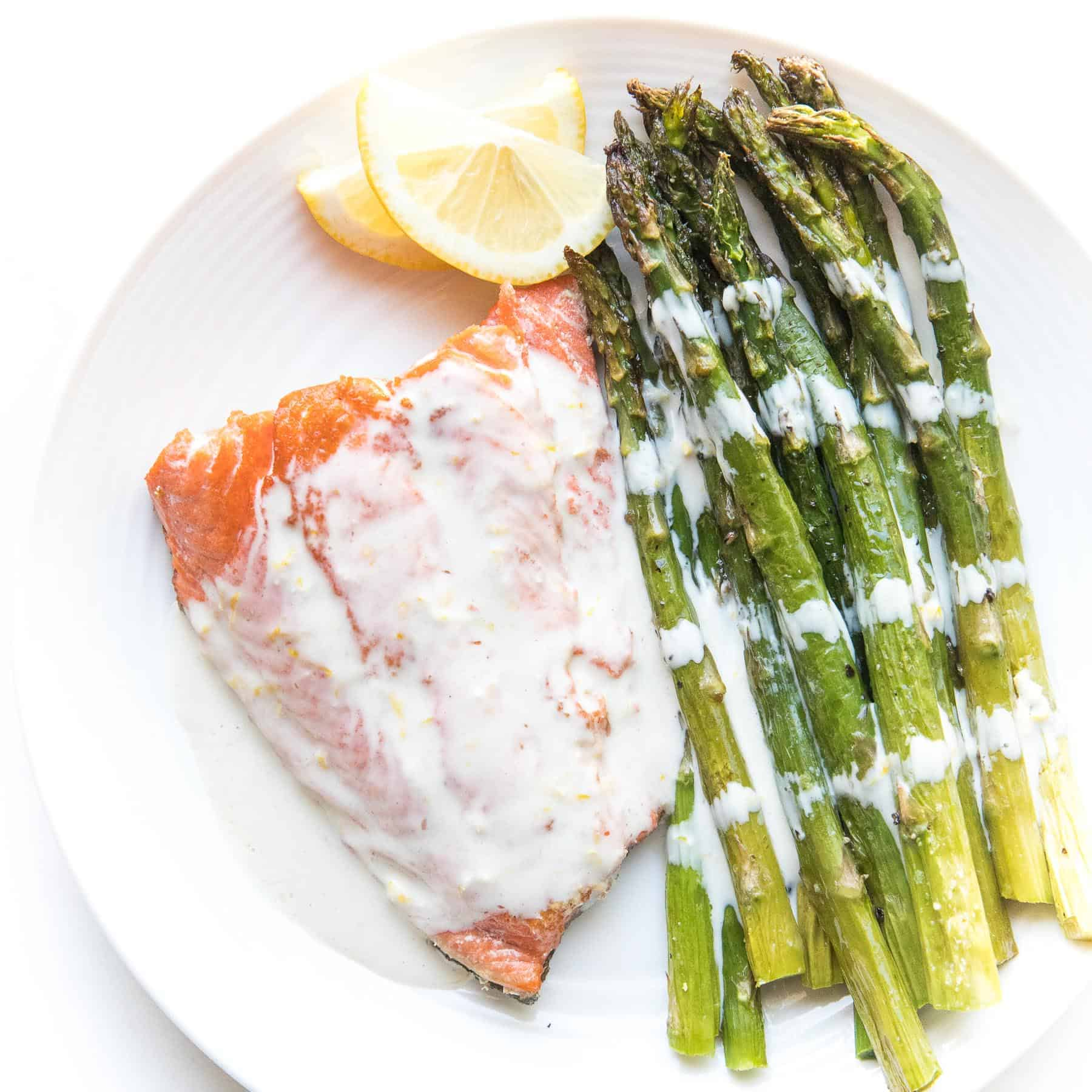 salmon with white sauce with lemon and asparagus on a white plate