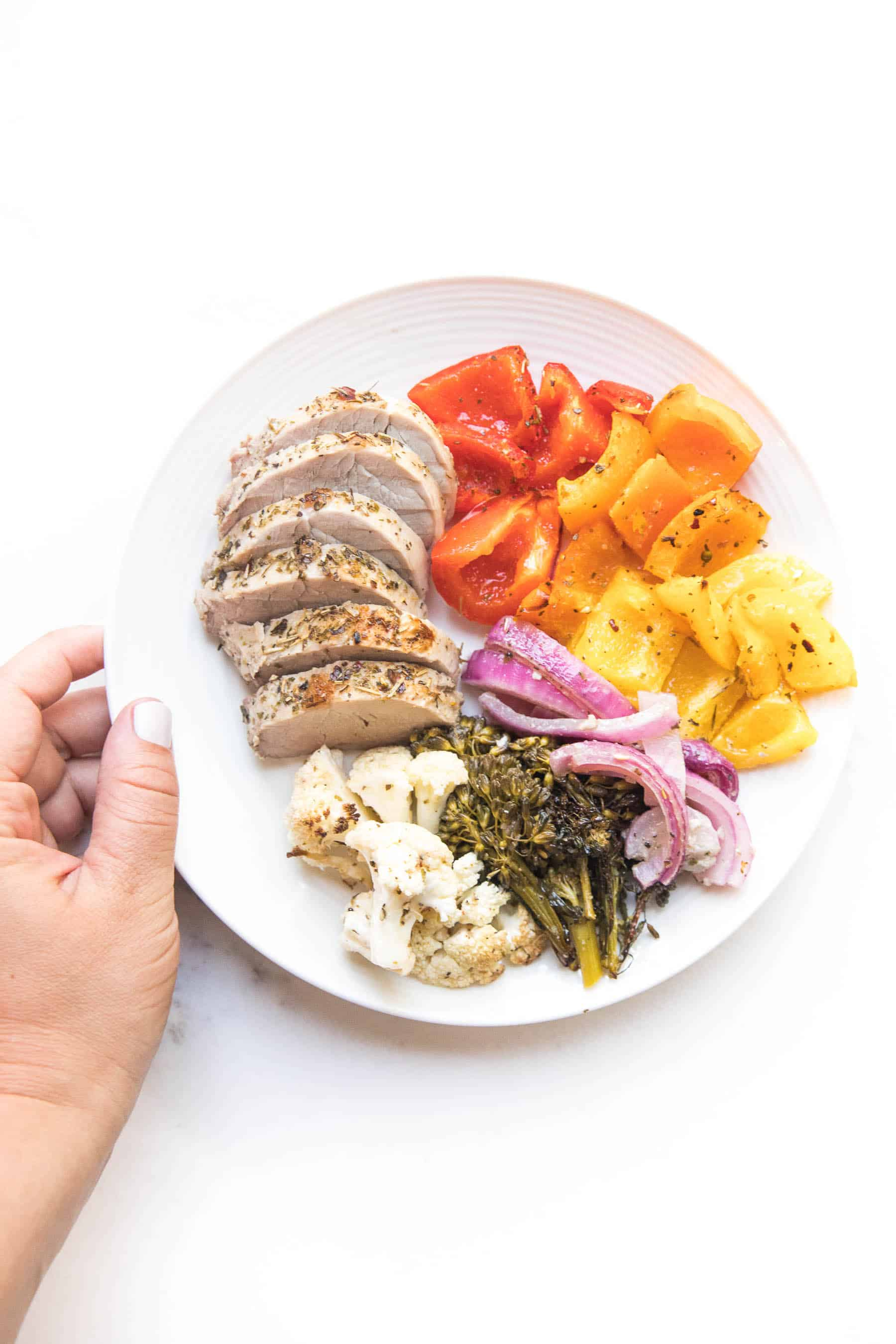 hand holding a white plate with sliced pork tenderloin and rainbow vegetables