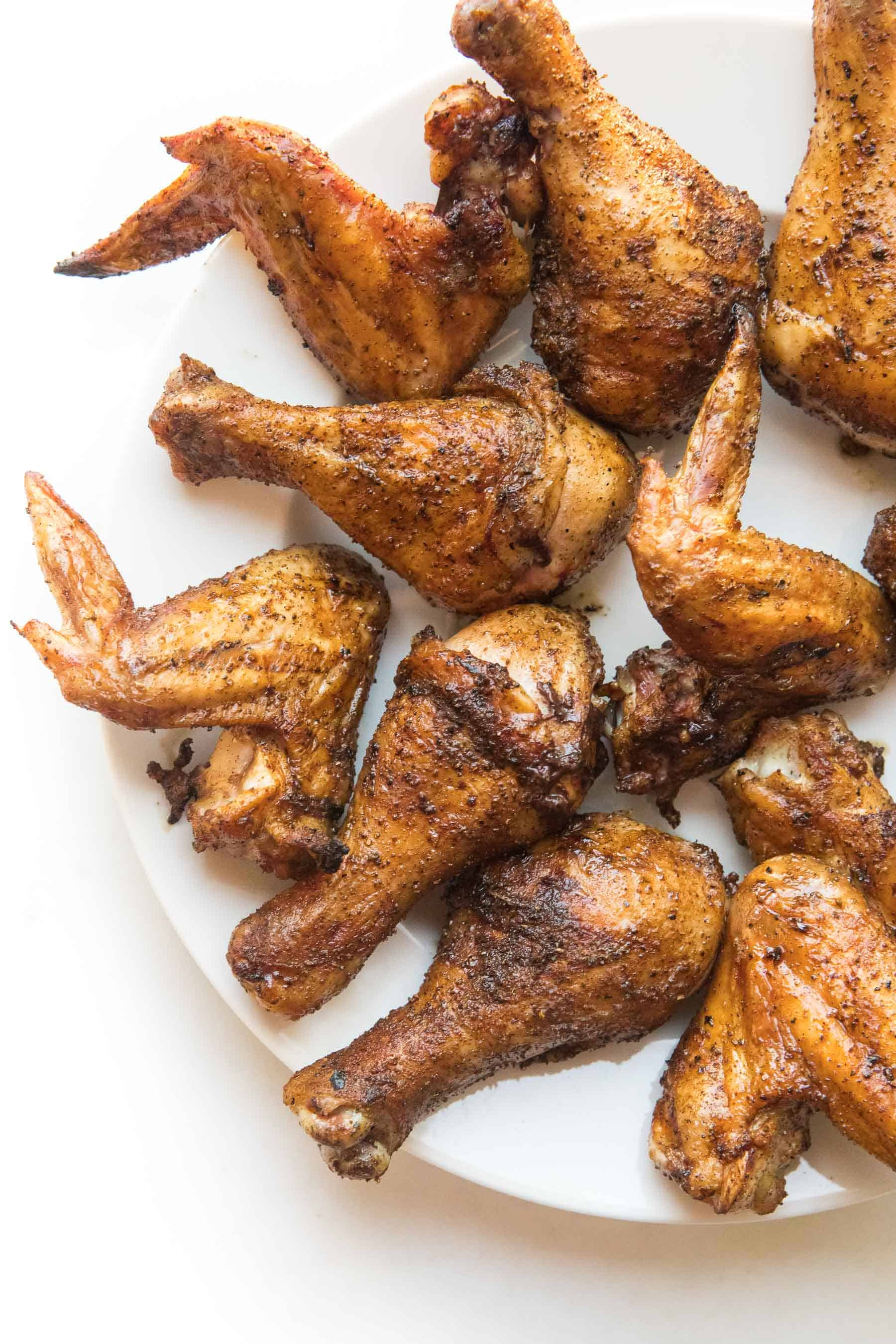 crispy roasted drumsticks + wings on a white plate and background