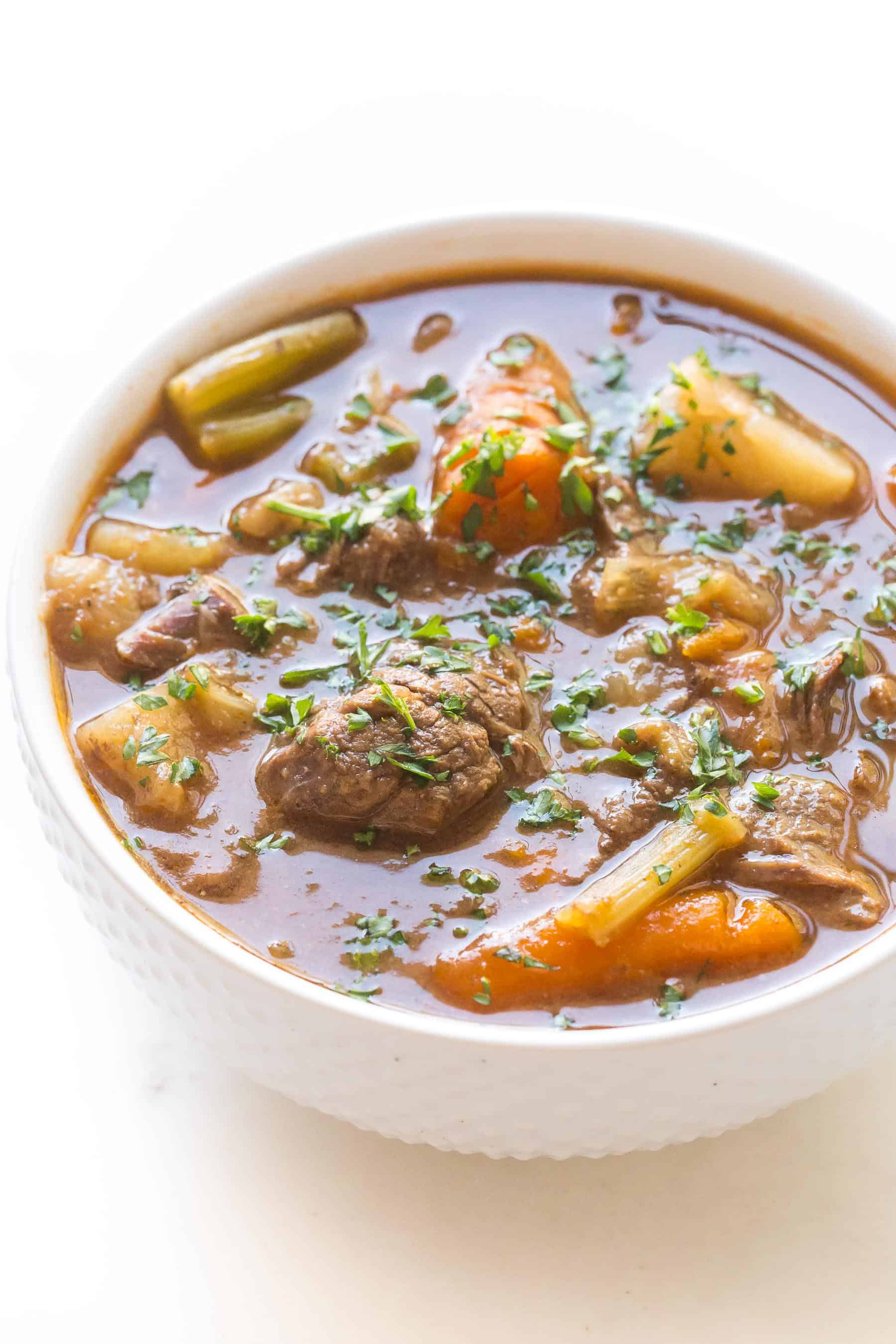 beef stew in a white bowl on a white background