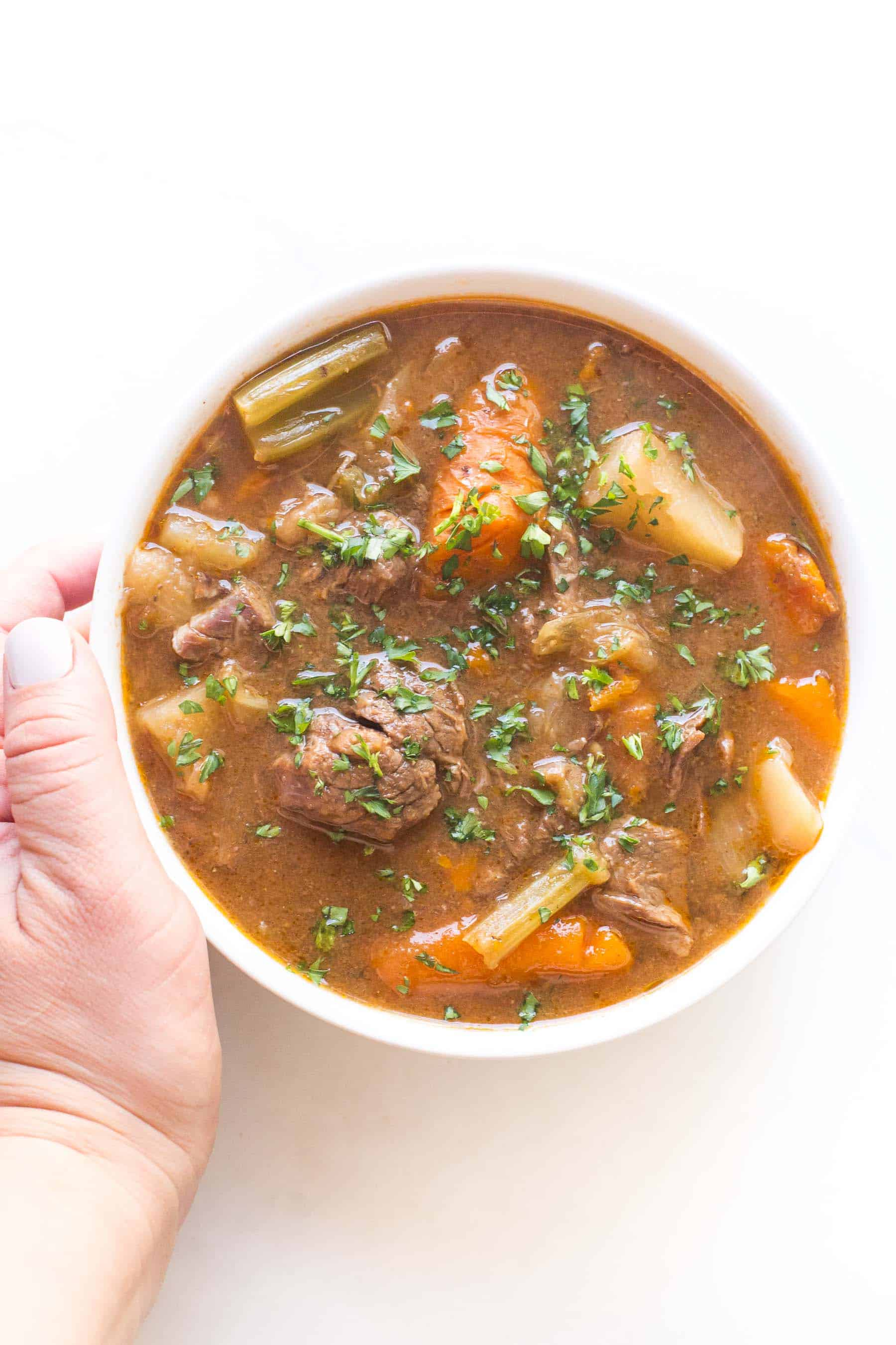 hand holding beef stew in a white bowl on a white background