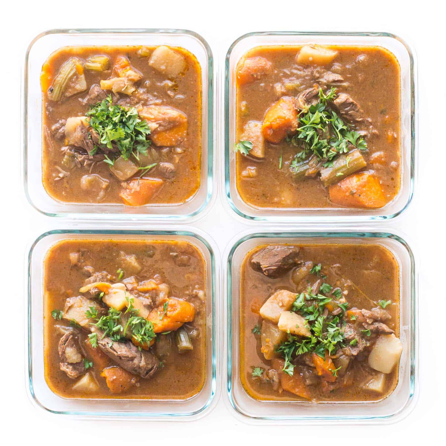 meal prep beef stew in meal prep containers l on a white background