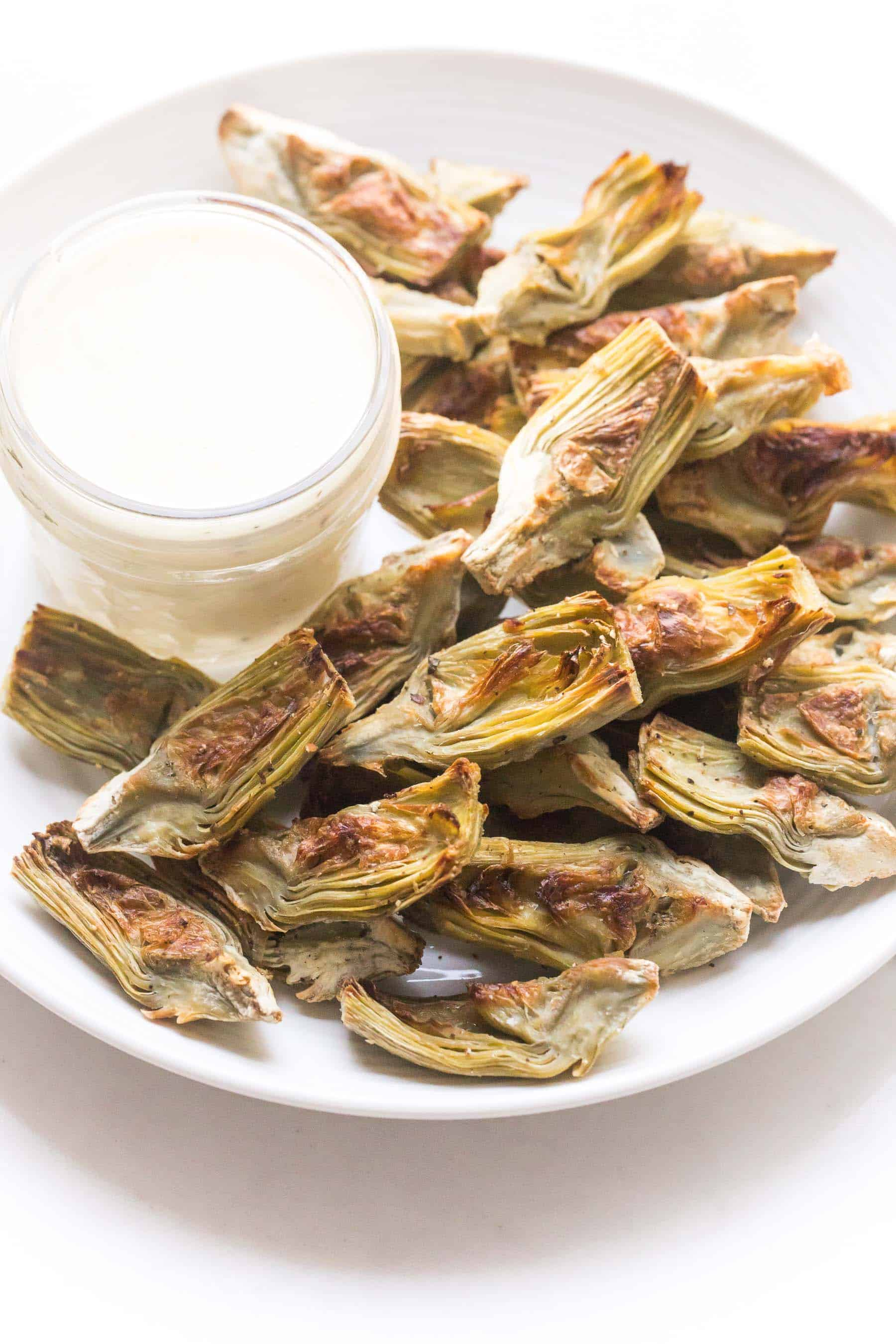 Roasted artichokes on a white plate with white lemon garlic aioli dipping sauce on a white background