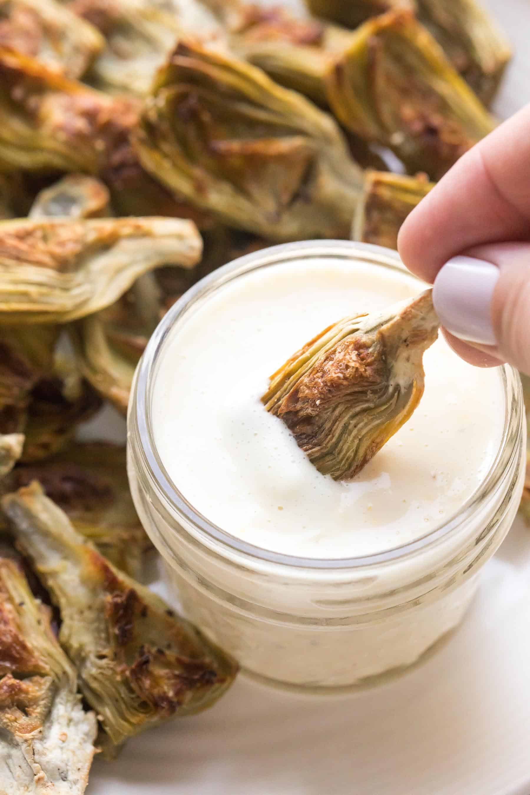 Roasted artichokes on a white plate with white lemon garlic aioli dipping sauce