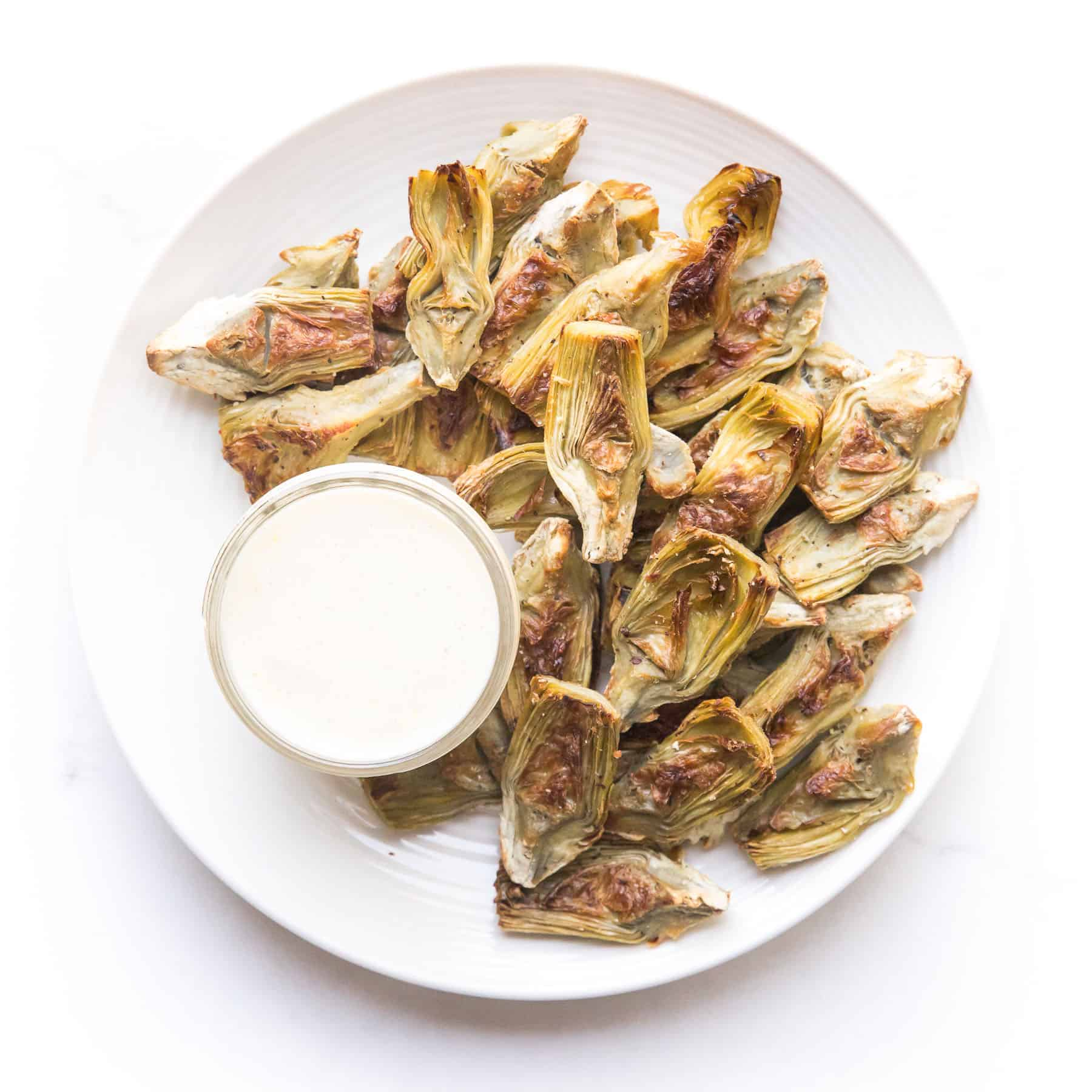roasted artichokes on a white plate with a white dip on a white background