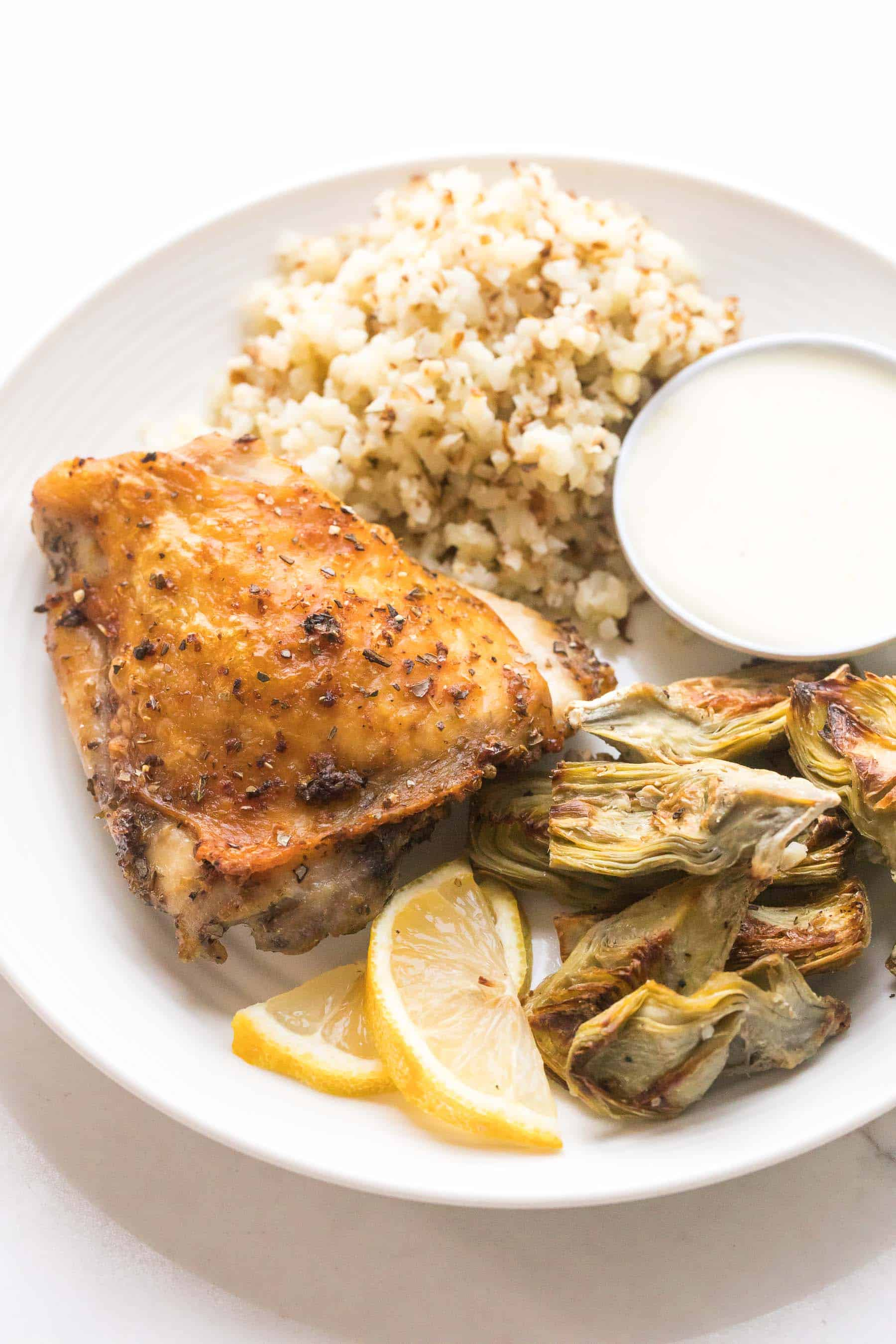 roasted chicken thigh, artichokes and cauliflower rice on a white plate