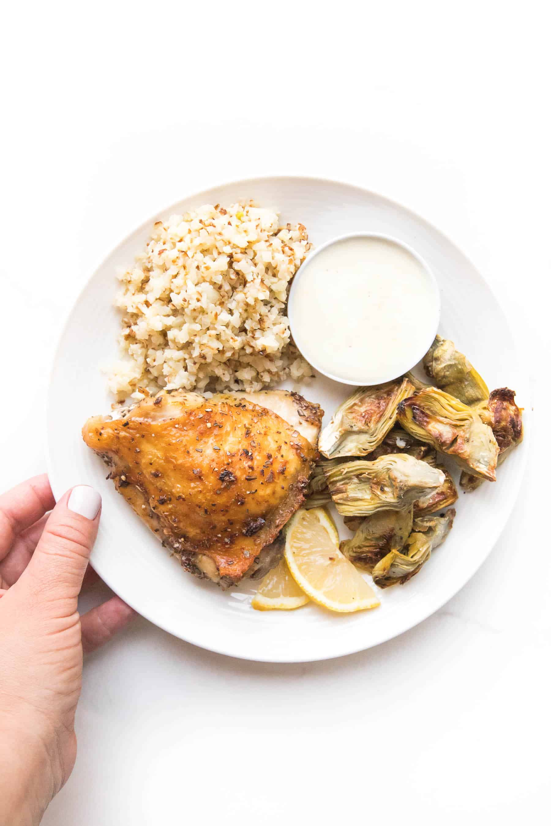 hand holding a white plate with chicken thigh, roasted artichoke hearts and cauliflower rice