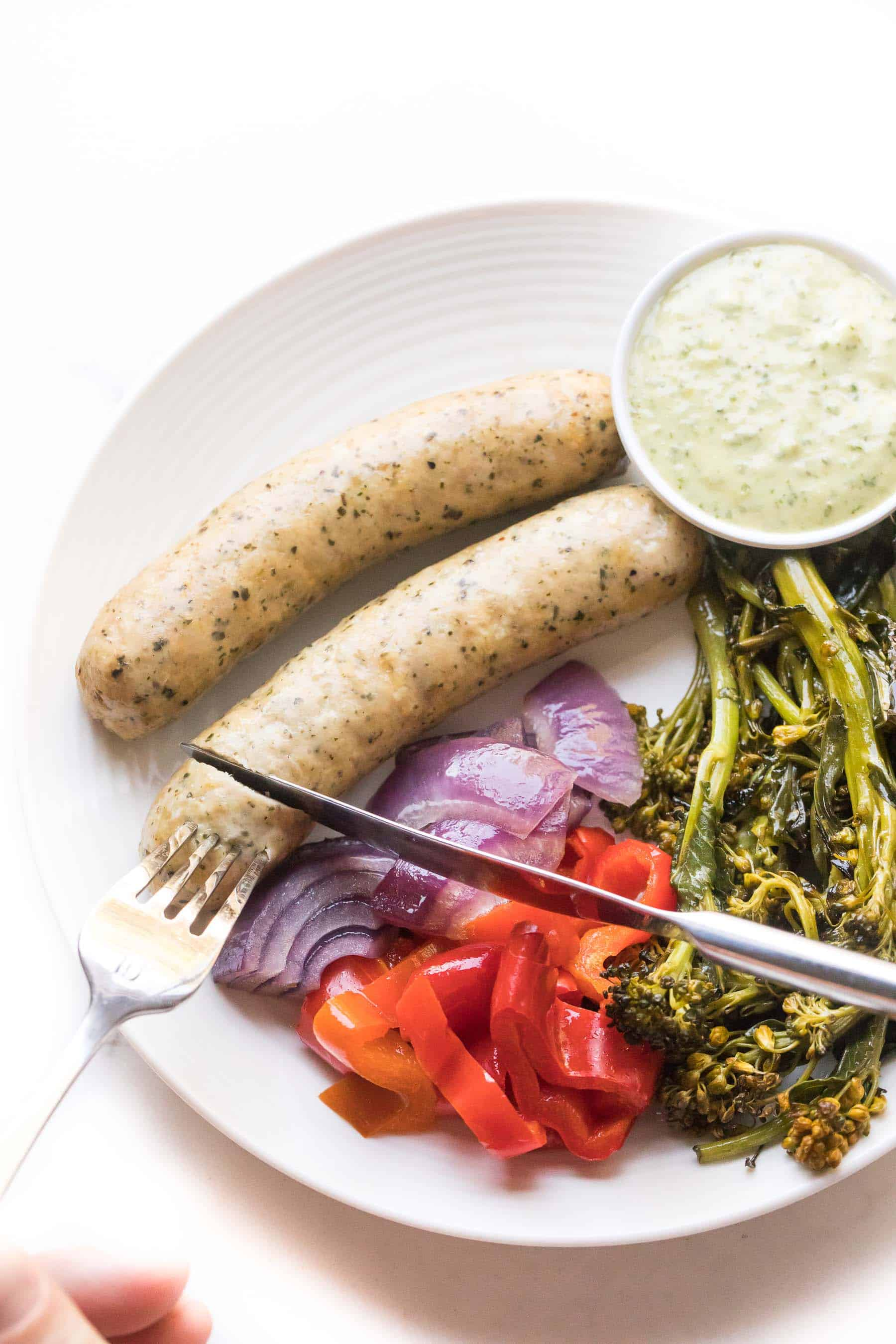 knife cutting sausages and vegetables on a white plate on a white background
