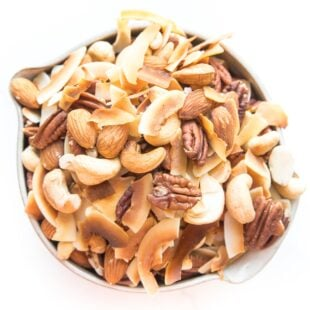 nuts and coconut chips trail mix in a bowl on white background