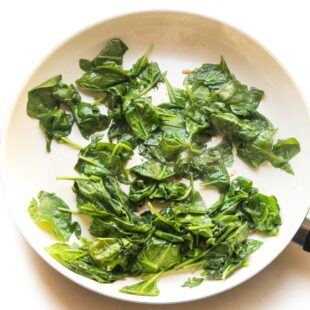 sauteed spinach in a white skillet