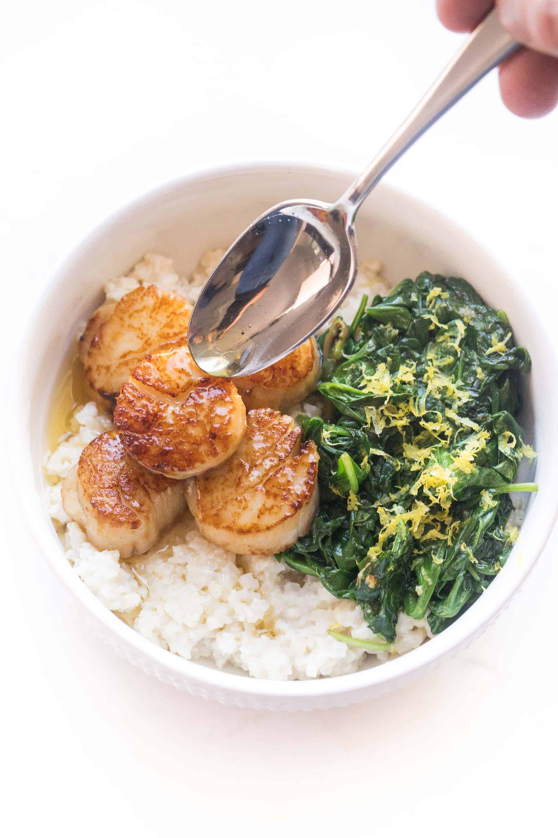 Seared scallops in a white bowl with cauliflower rice risotto + sauteed spinach
