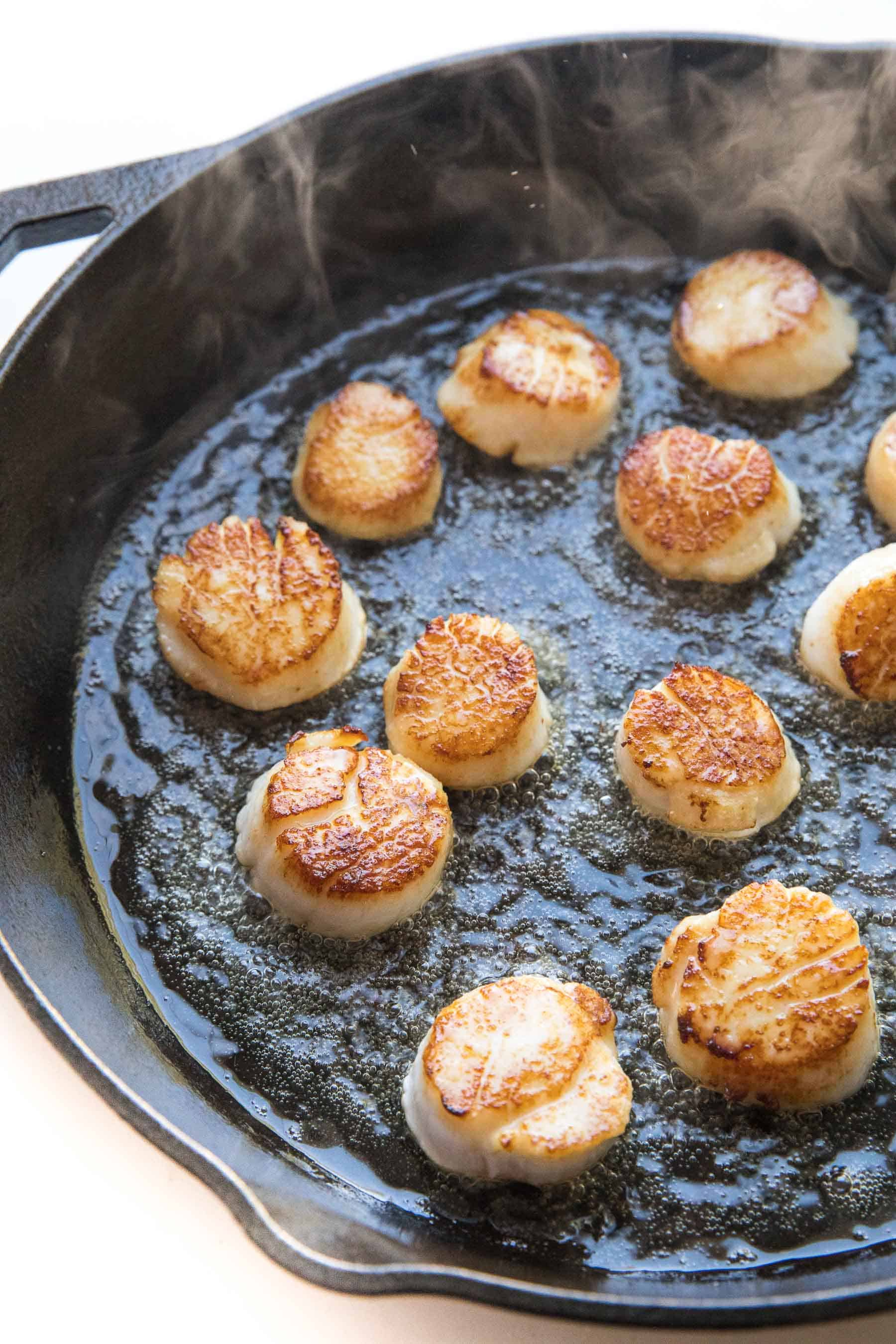 scallops searing in a cast iron skillet