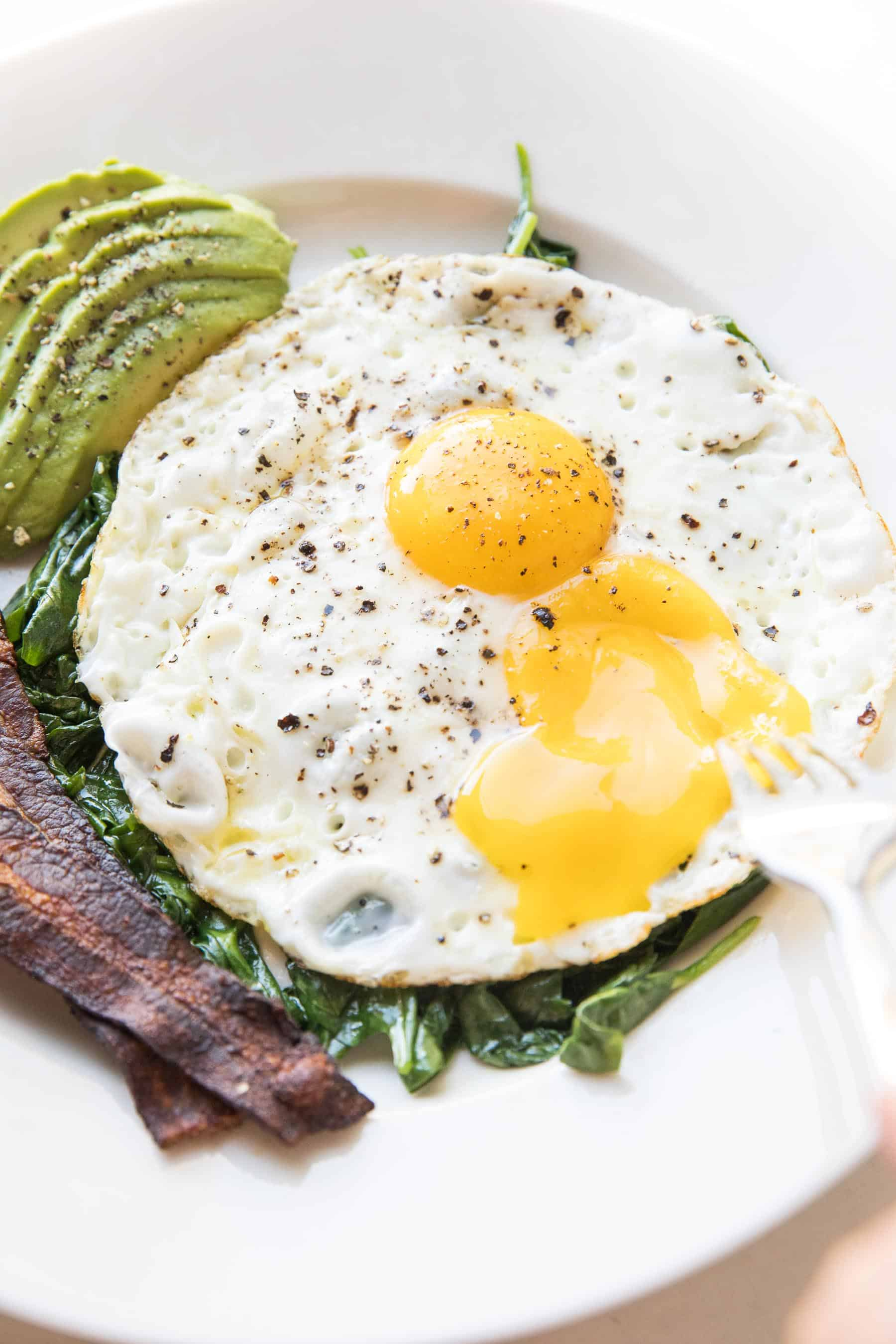 fork breaking sunny side up eggs with sauteed spinach, bacon + avocado