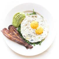 sunny side up eggs with sauteed spinach, bacon + avocado
