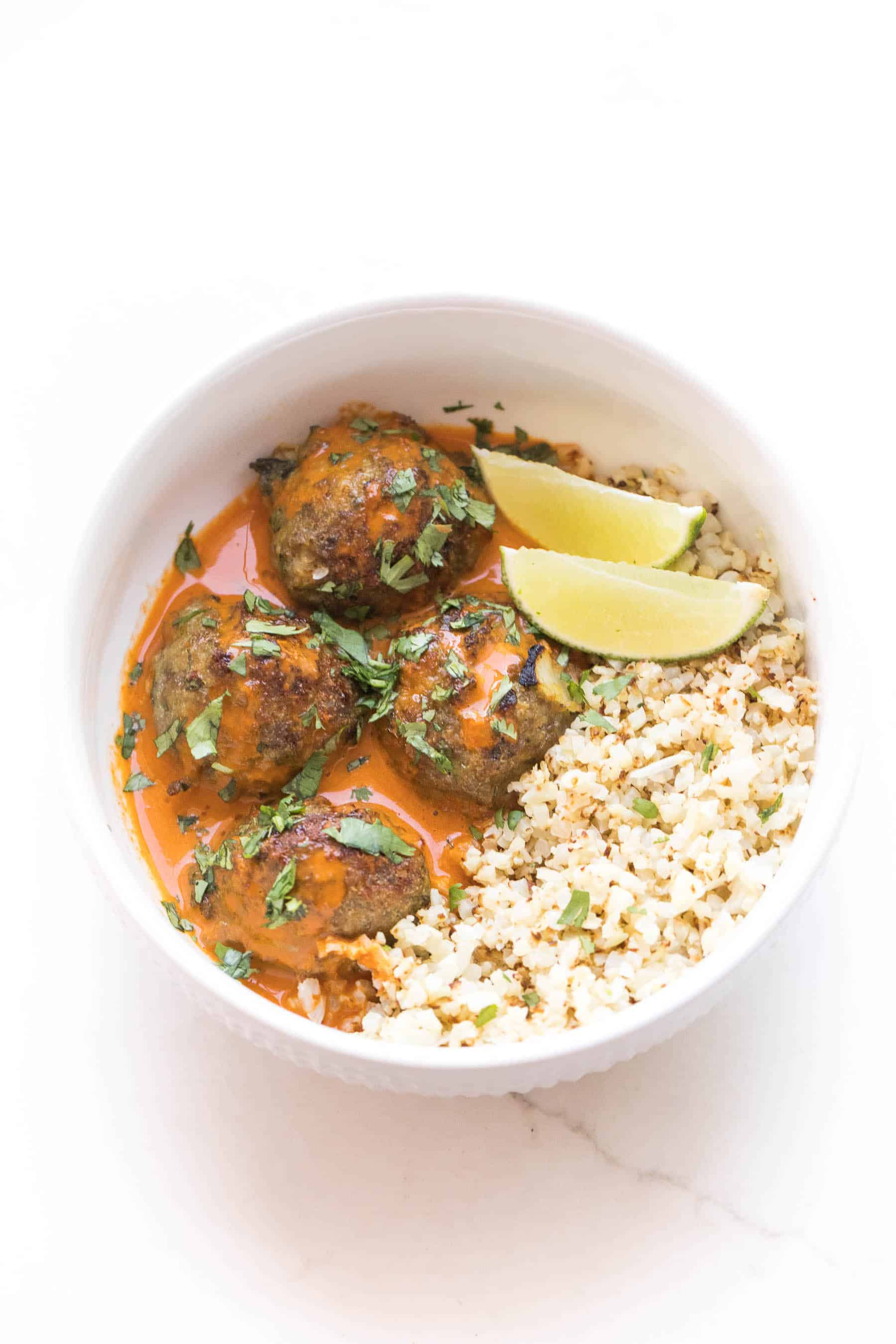 thai curry meatballs in a white bowl with thai curry sauce