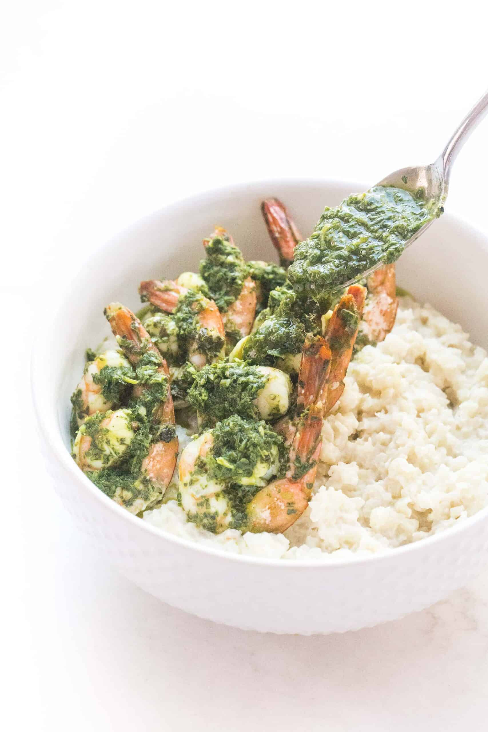 pouring chimichurri on shrimp on cauliflower rice risotto