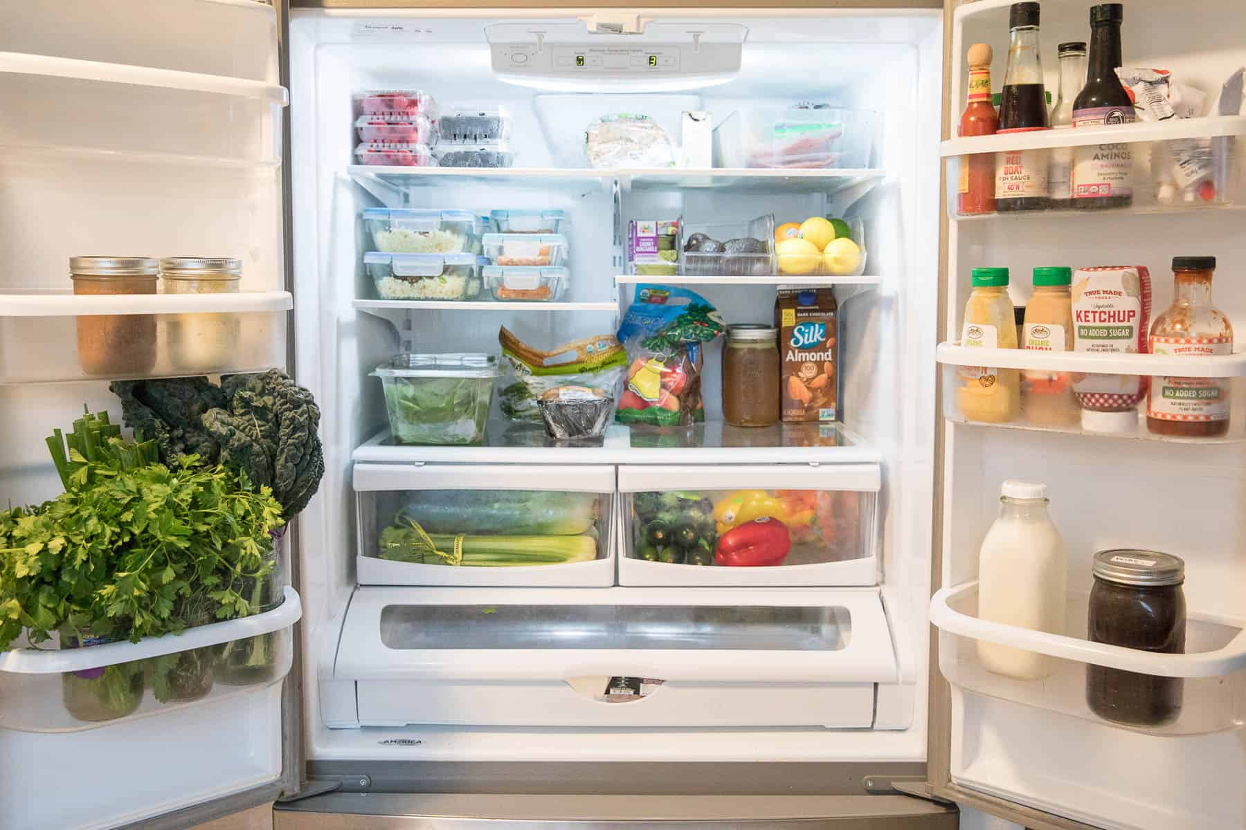 organized keto refrigerator with produce, meal prep, condiments