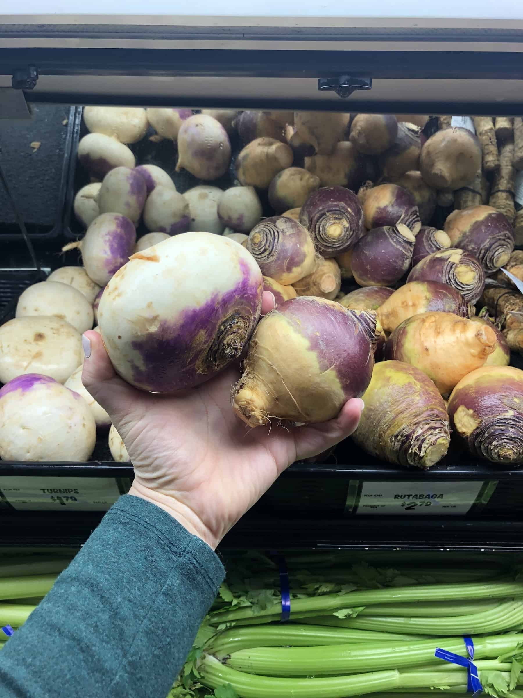 turnips and rutabagas being held in a hand at a grocery store