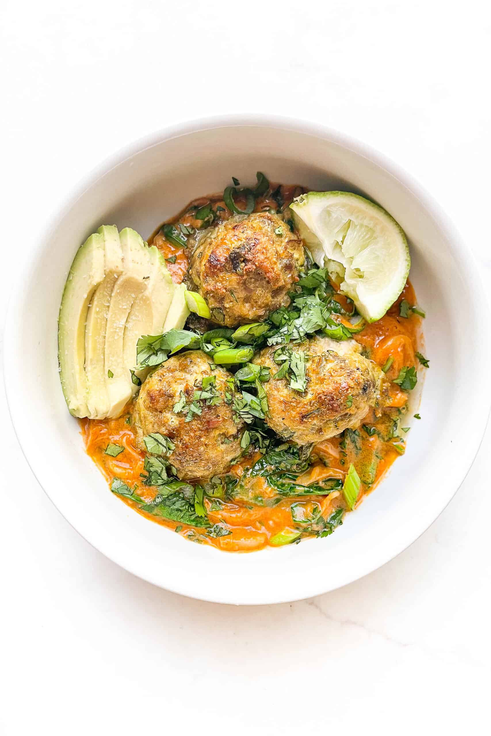 thai curry meatballs over noodles and curry sauce in a white bowl