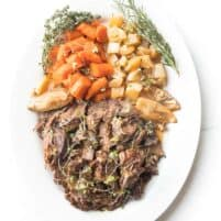 pot roast on a white plate with fresh herbs