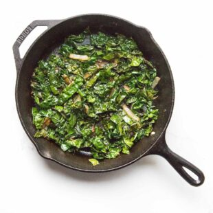 sauteed kale in a cast iron skillet