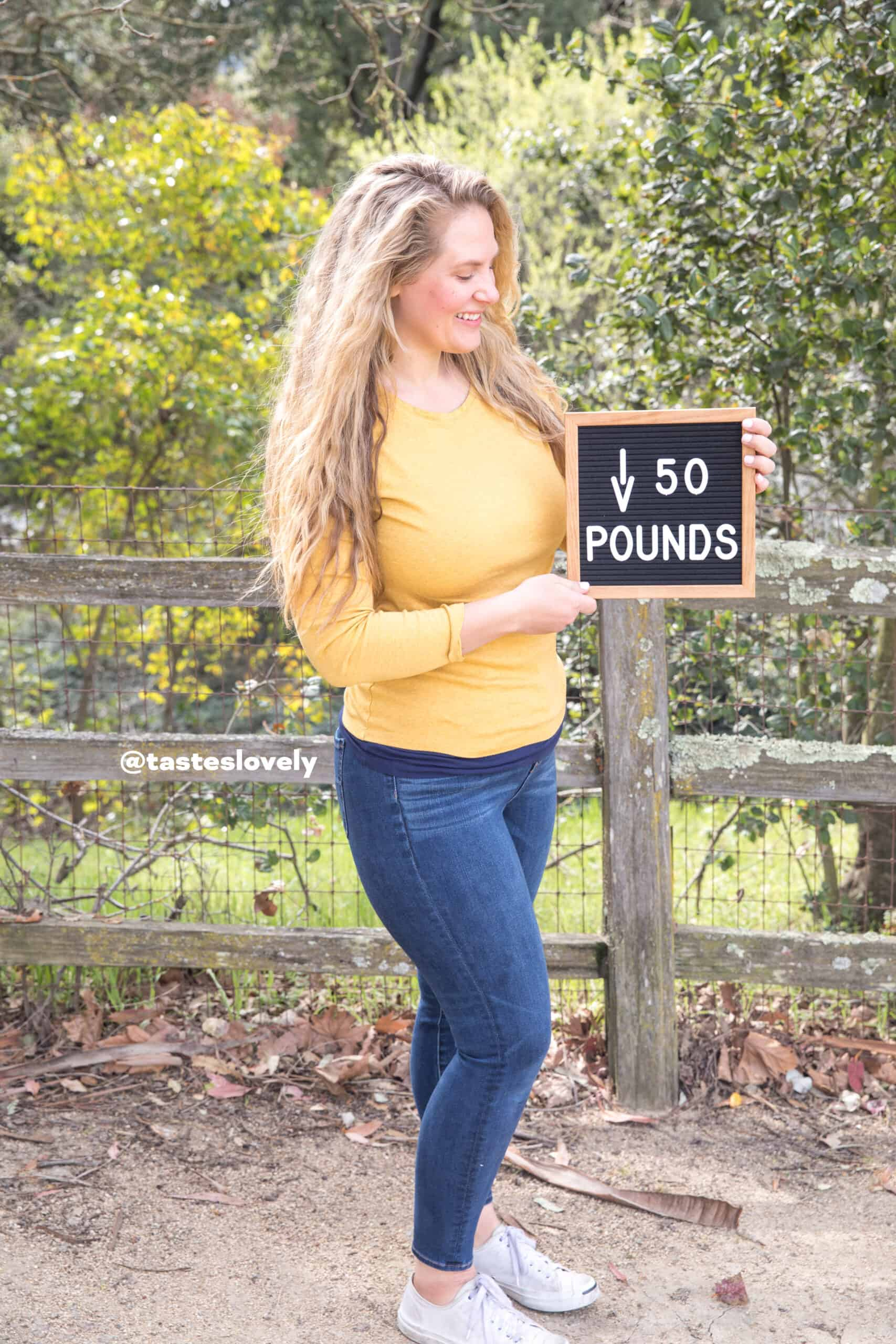 how i lost weight eating clean keto, girl holding a sign saying down 50 pounds weight loss