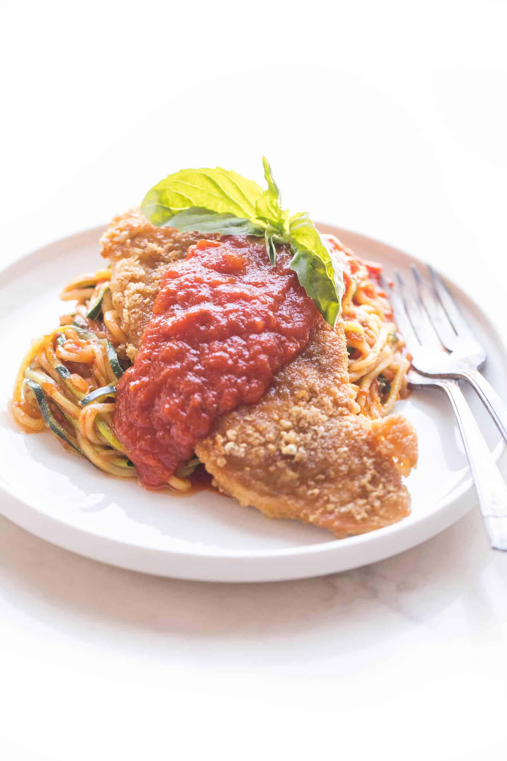 chicken parmesan topped with marinara sauce over zucchini noodles on a white plate and background