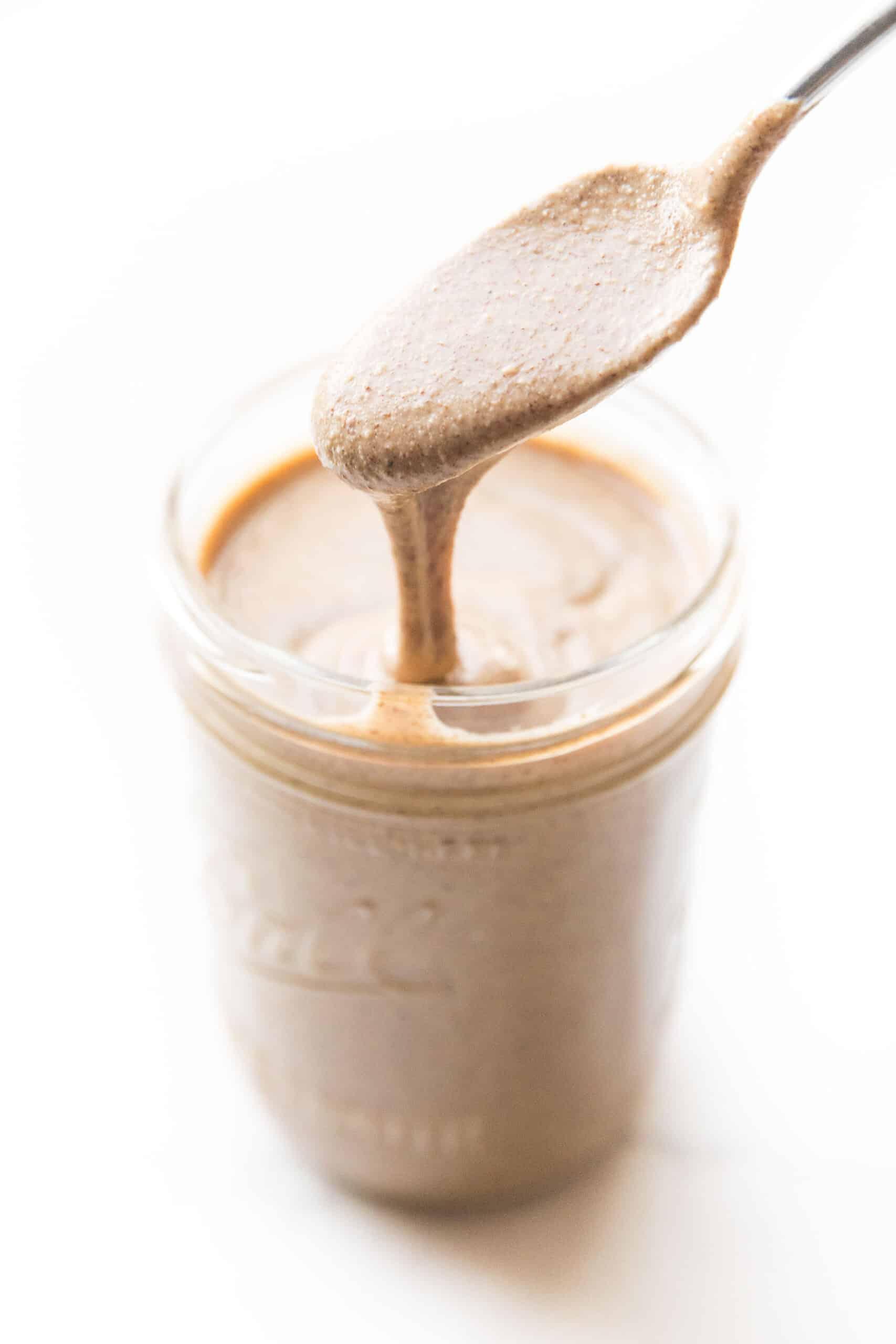 spoon drizzling nut butter in a mason jar