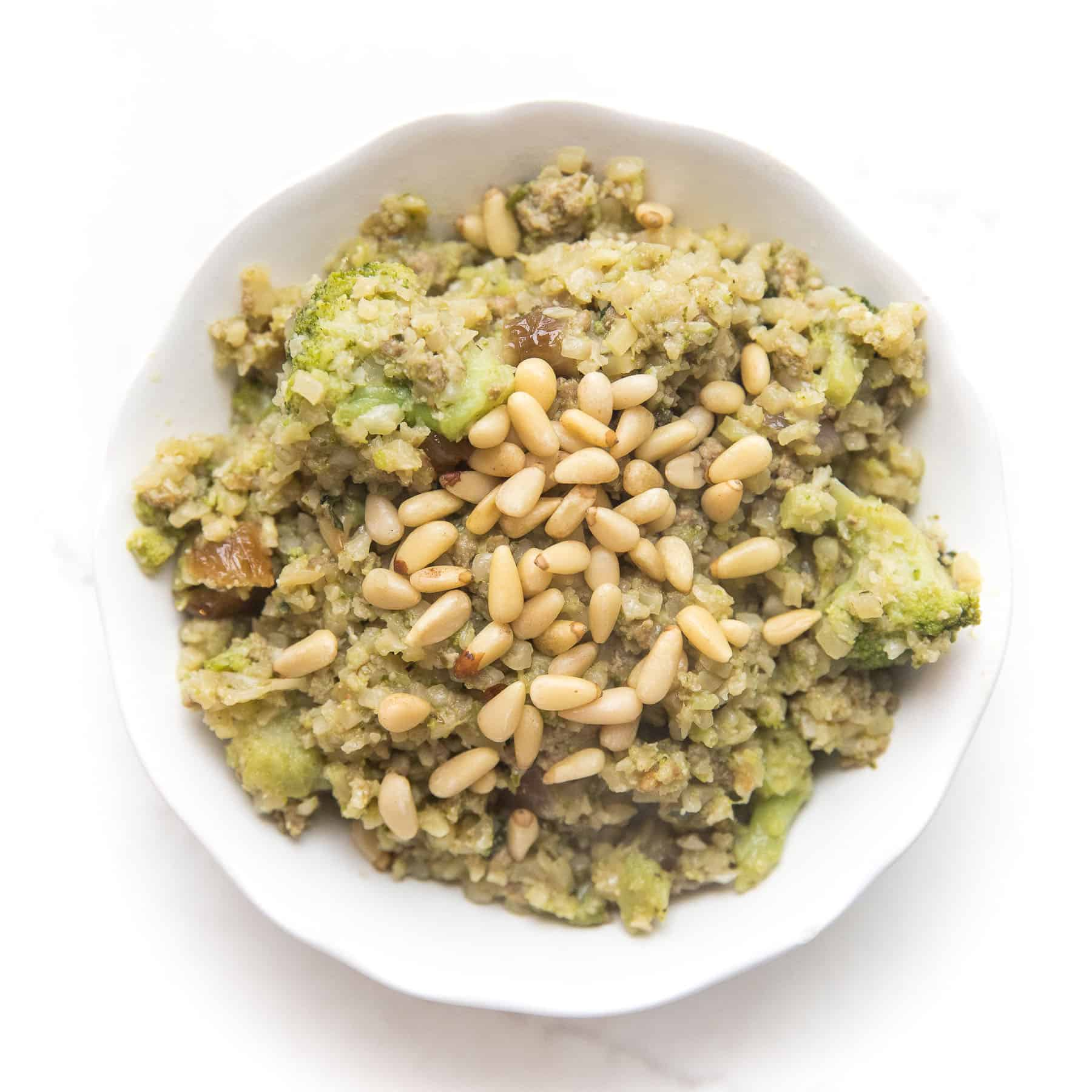pesto cauliflower rice, broccoli, meatballs and pinenuts in a white bowl