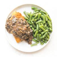breaded chicken with mushroom gravy on a white plate with green beans