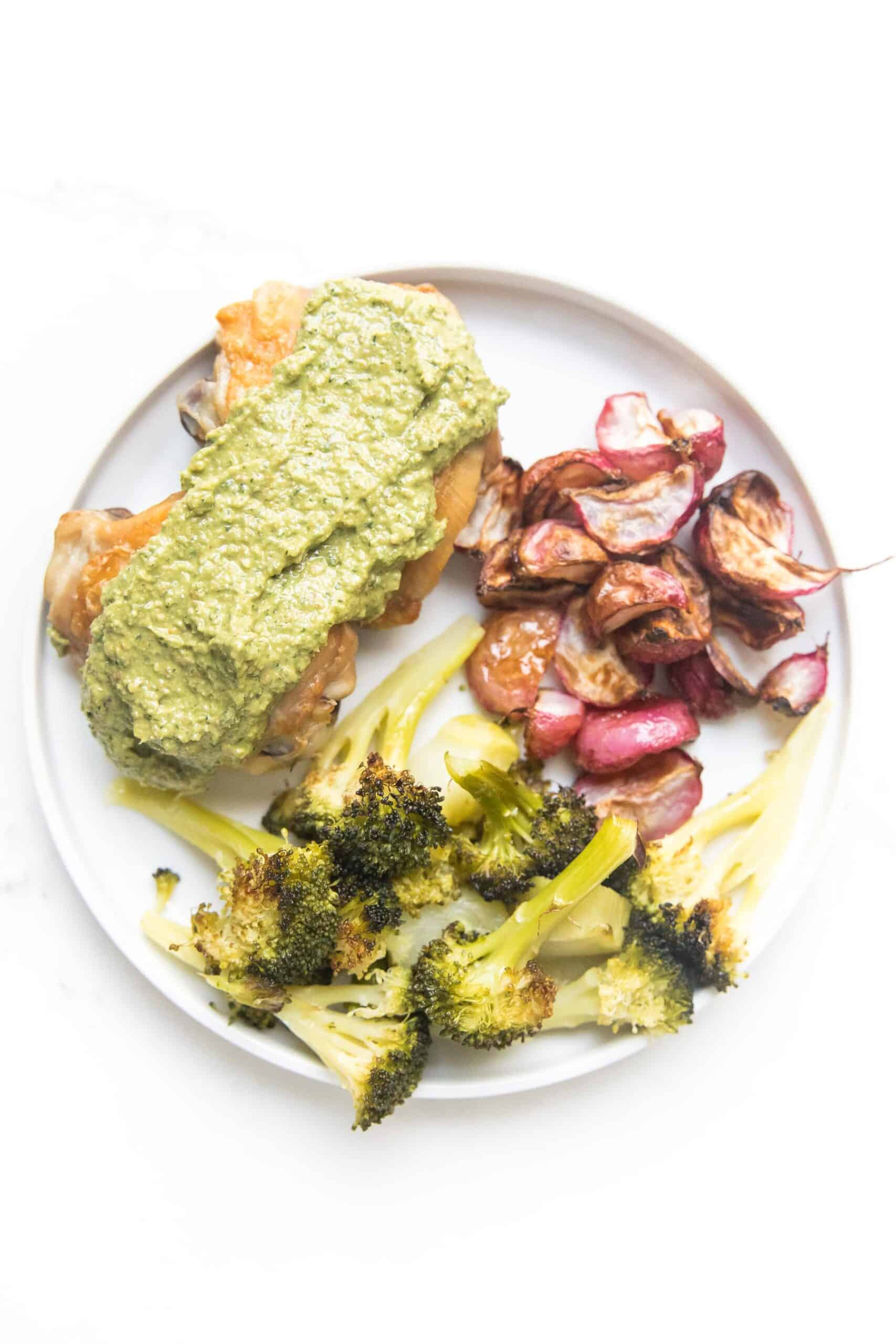 chicken thighs with a green sauce, broccoli and roasted radishes on a white plate