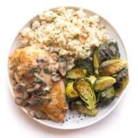 chicken with mushroom gravy on a white plate and background with roasted brussels sprouts and cauliflower rice