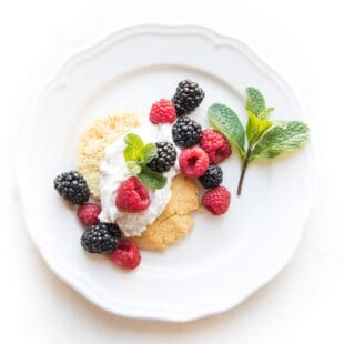 keto berry shortcake biscuit topped with whipped cream and raspberries and blackberries and mint on a white plate
