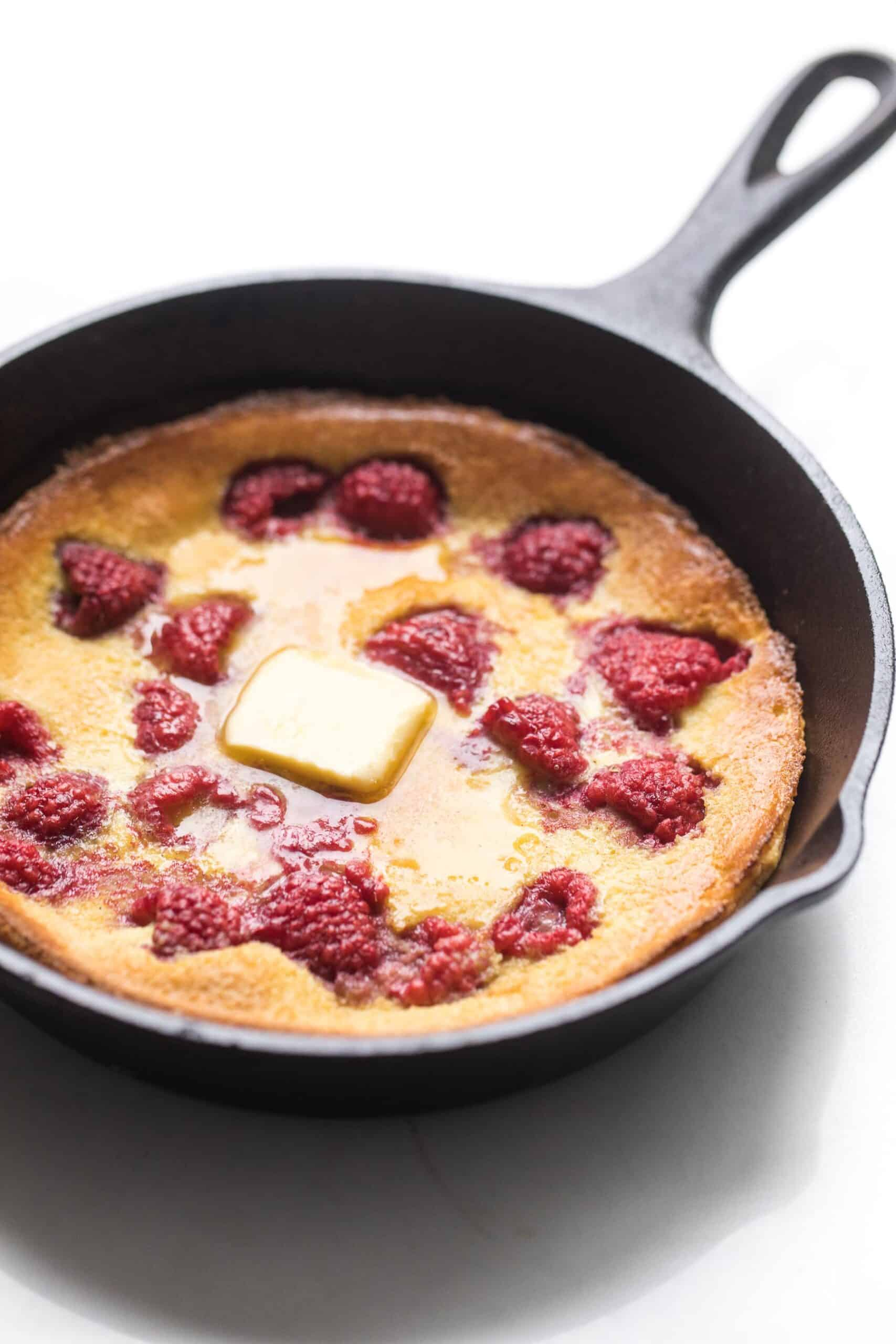keto dutch baby pancake in a cast iron skillet with raspberries