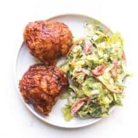bbq chicken thighs on a white plate with a green salad