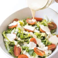 Pouring caesar dressing over salad