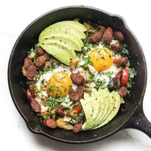 KETO low carb no potato breakfast hash with eggs and avocado in a cast iron skillet on a white background