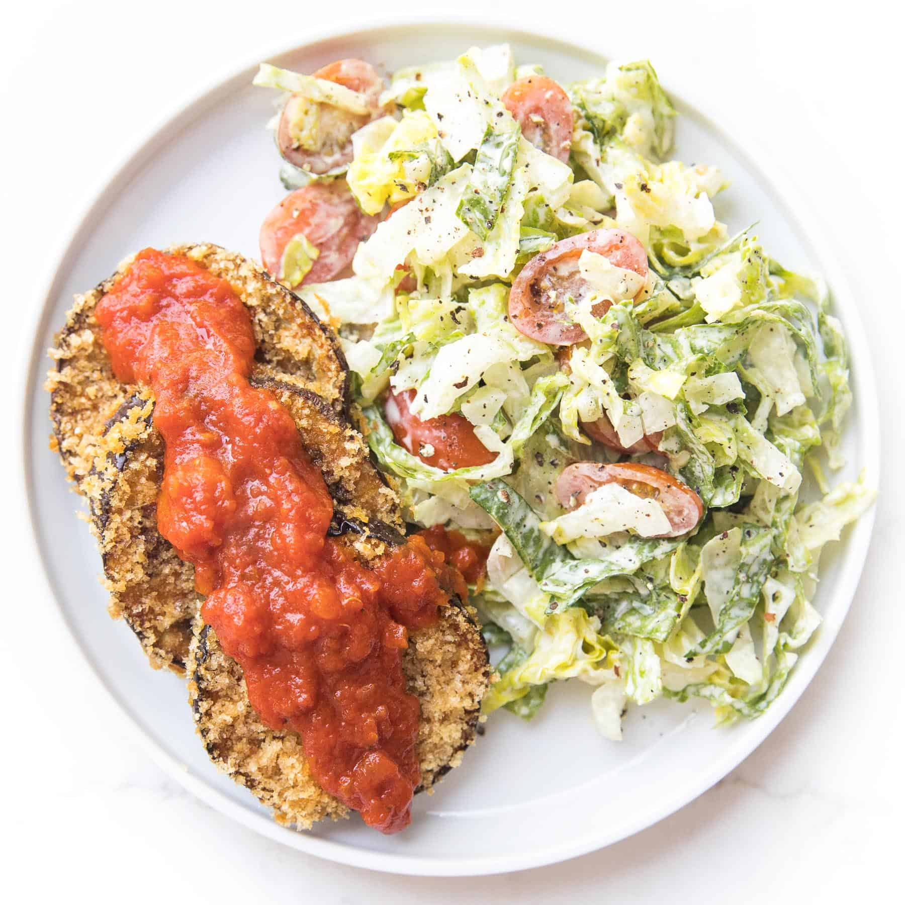 crispy coated eggplant next to caesar salad on a white plate