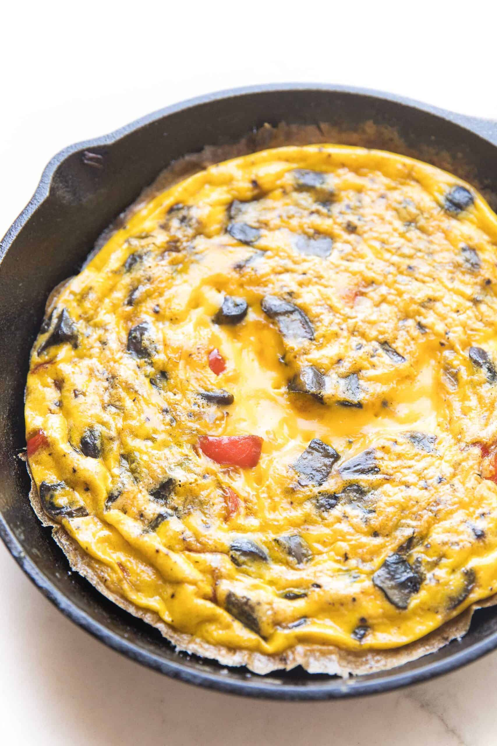 frittata in a cast iron skillet and white background
