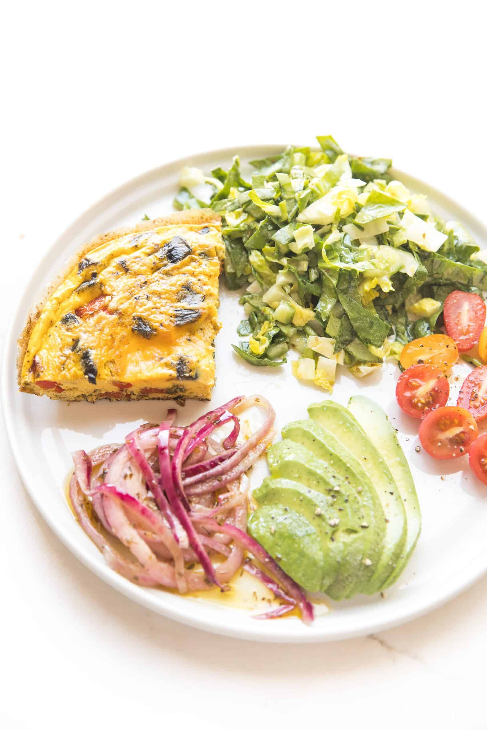 frittata on a white plate with marinated onions, avocado, tomatoes, green salad