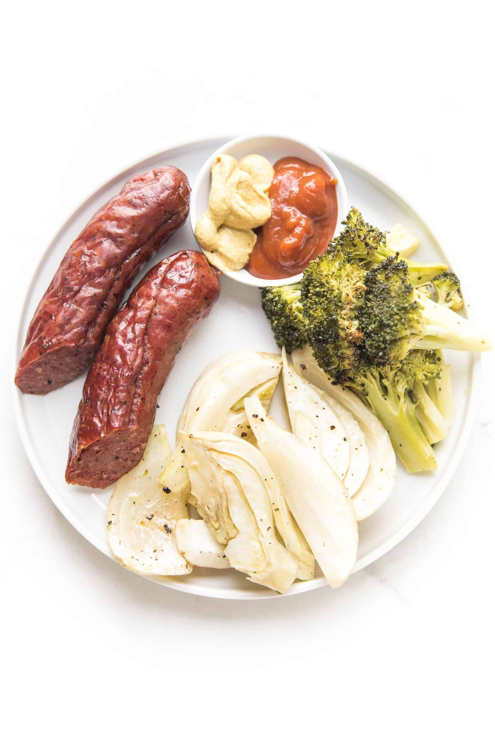 sausage, roasted fennel and broccoli on a white plate and background