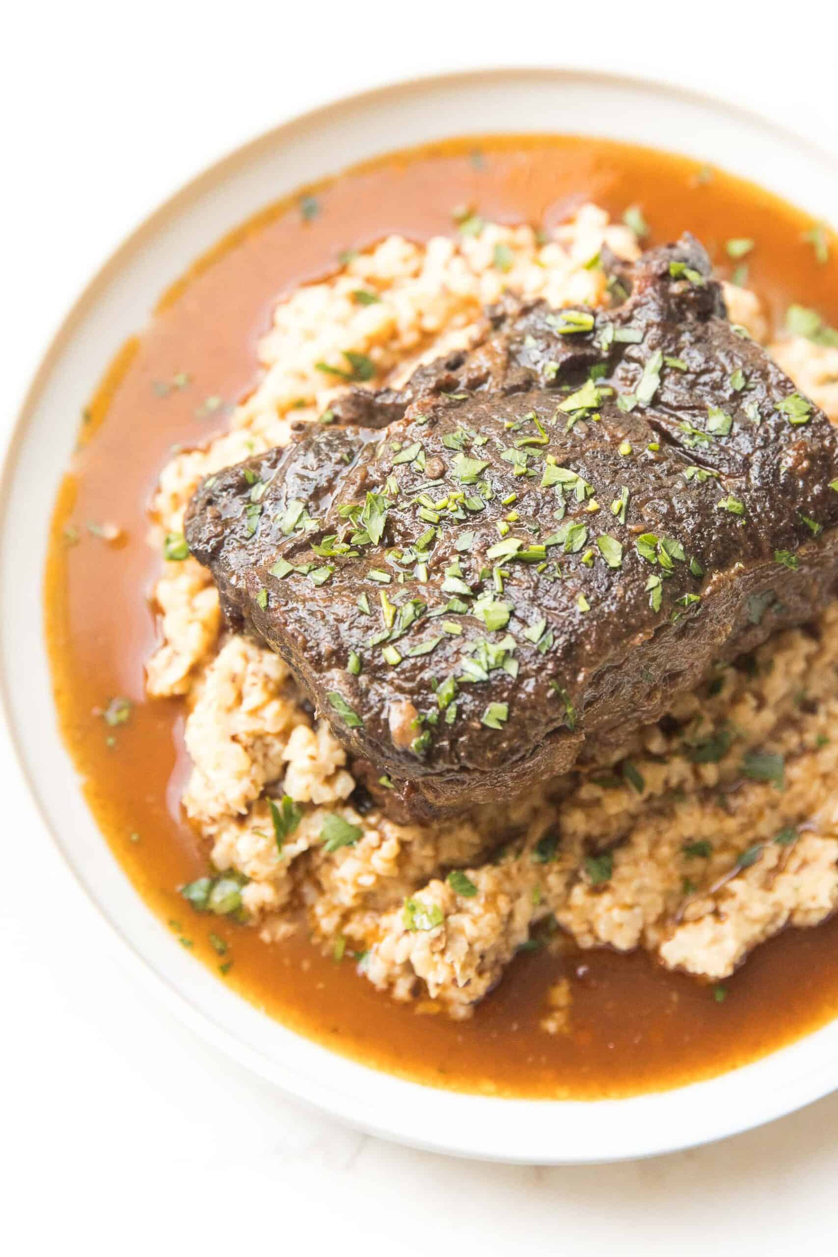 SHORT RIBS AND CAULIFLOWER RICE RISOTTO ON A WHITE PLATE AND BACKGROUND