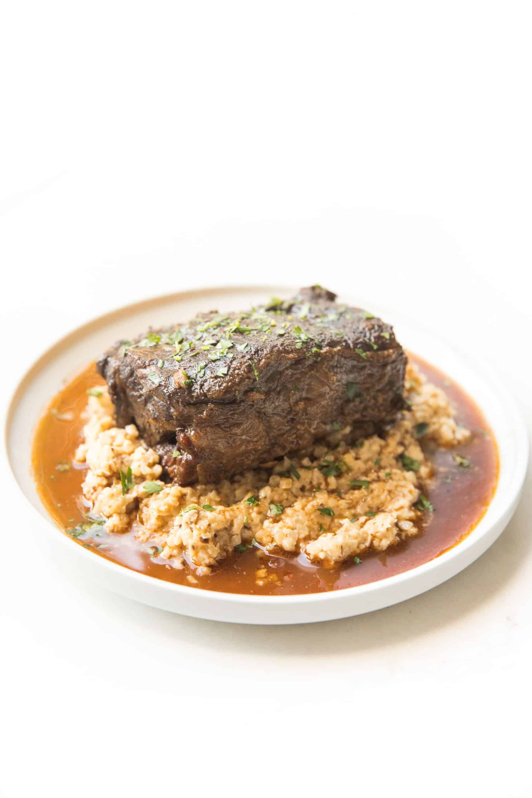 BRAISED SHORT RIBS OVER CAULIFLOWER RICE RISOTTO ON A WHITE PLATE AND BACKGROUND